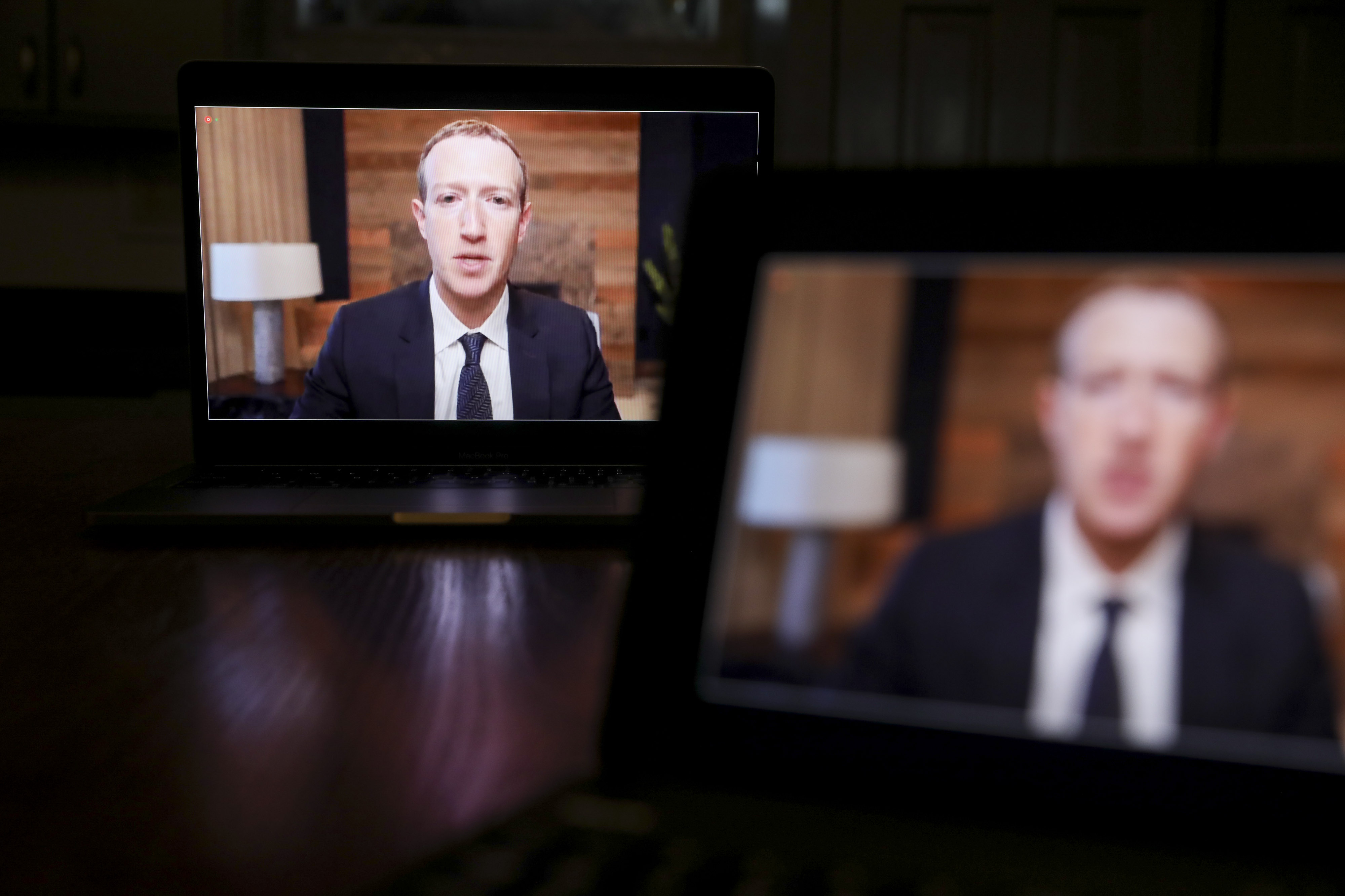 Facebook CEO Mark Zuckerberg on two laptop screens at a congressional hearing.