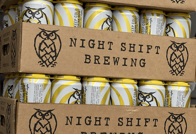 "A stack of beer cans inside a cardboard container. The container reads, ""Night Shift Brewing,"" and the cans are adorned with a graphic owl logo."