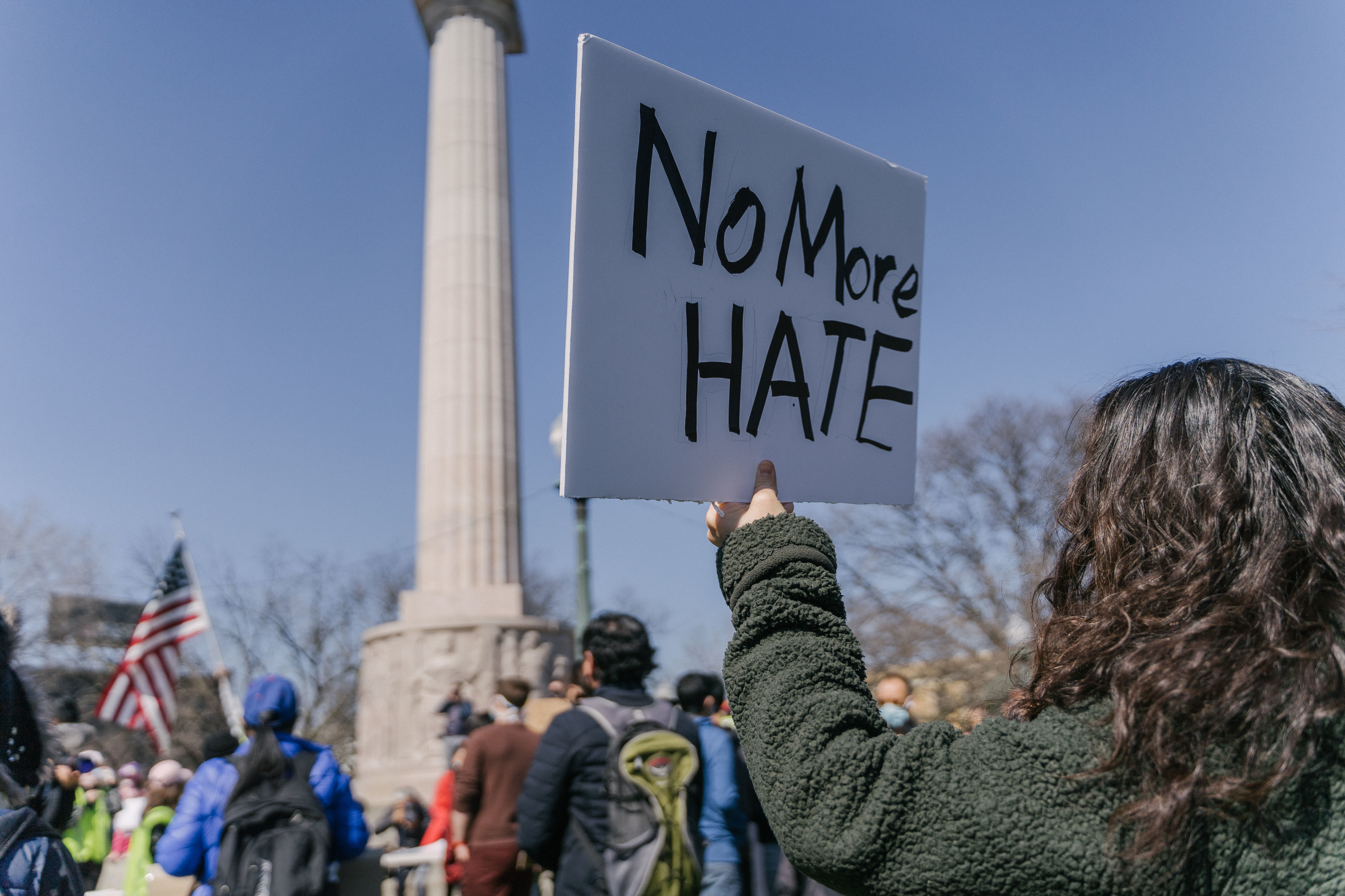 Li Liu, 48, raises a sign during a Stop Asian Hate March at the Illinois Centennial Monument in Logan Square on March 20.