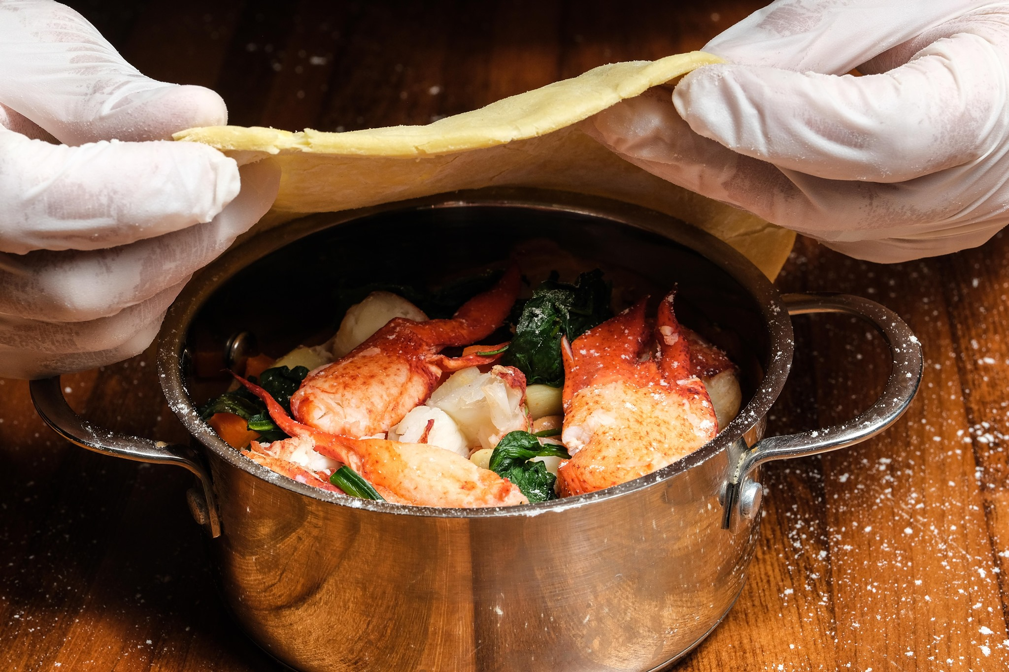 A lobster pot pie with two hands pulling dough over the top
