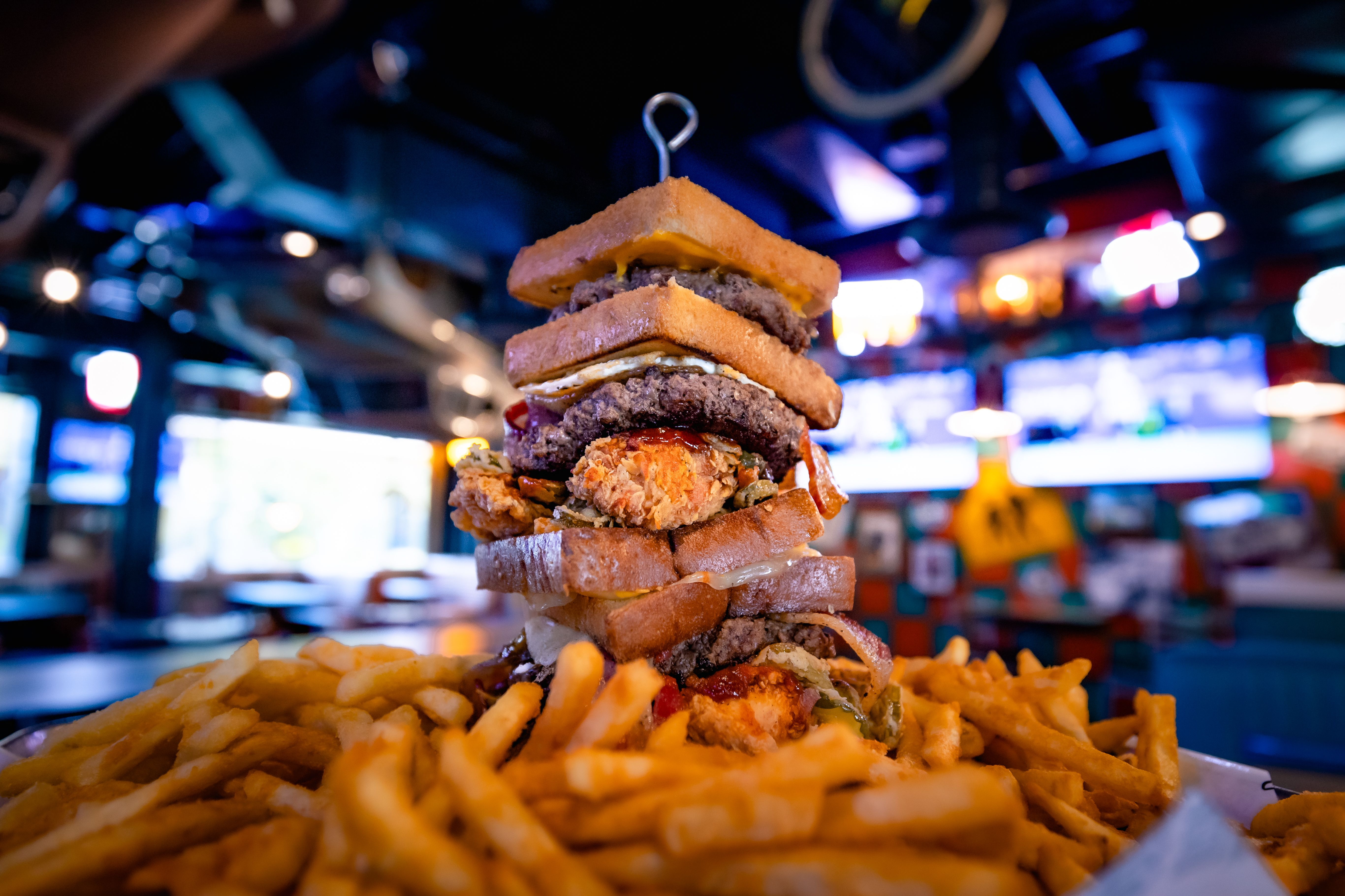 A food challenge burger with a massive patty melt on the exterior, a grilled cheese sandwich in the middle, and pulled pork, bacon, more burger patties, two fried eggs, fried jalapeños, fried pickles, boneless chicken wings, and barbecue and Sriracha sauces.