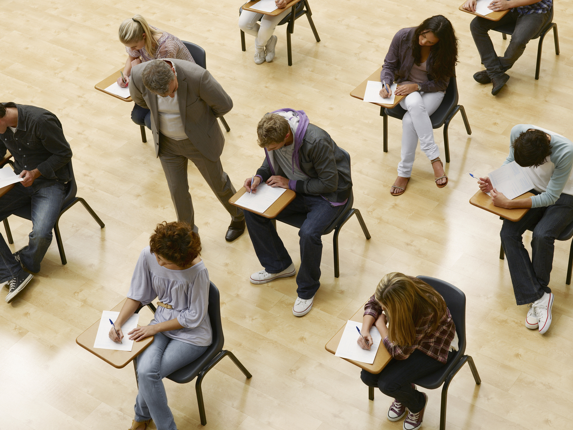 A group of students take a test in a classroom with a teacher walking by.
