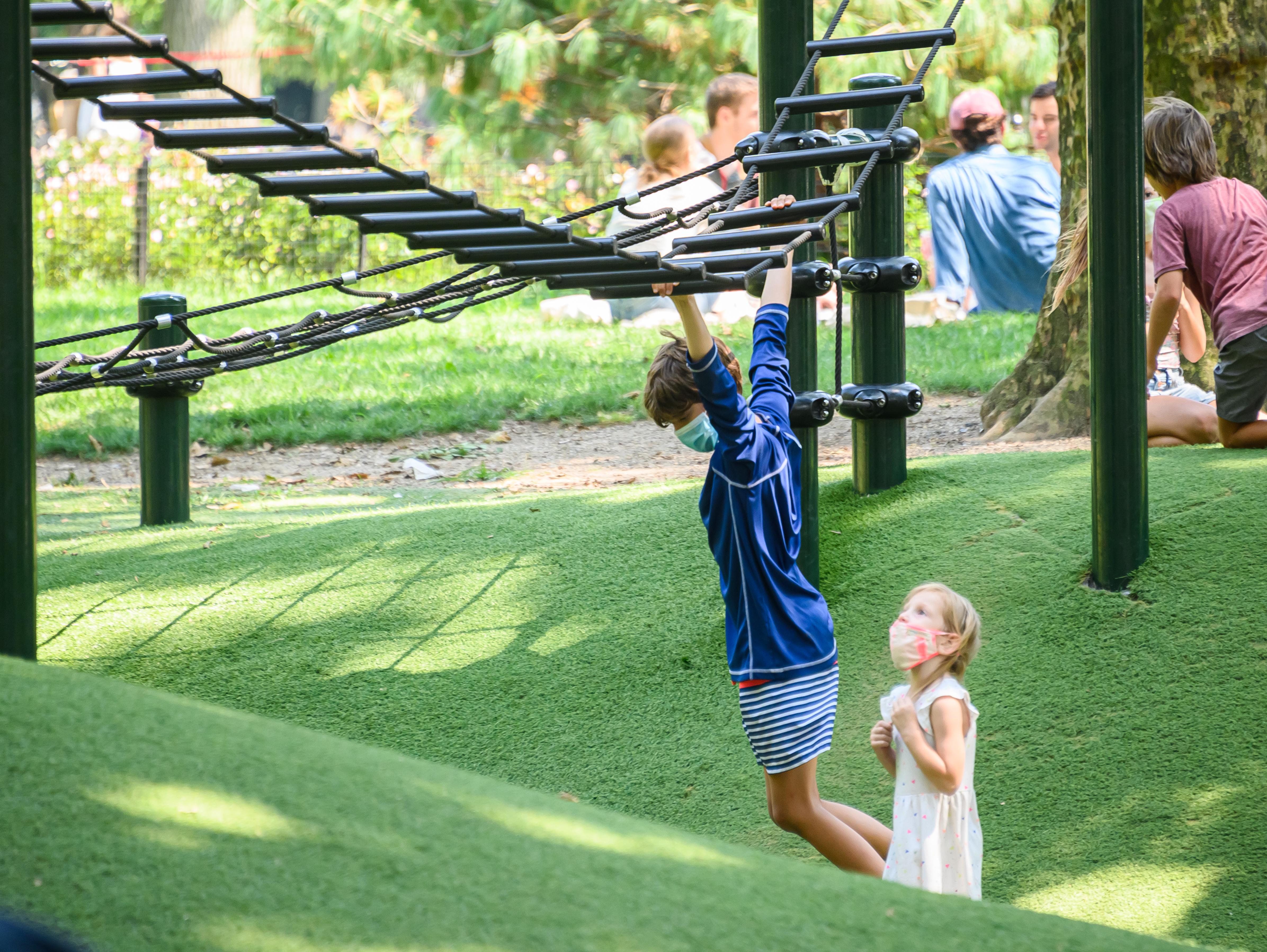 Children playing on a playground wearing masks.