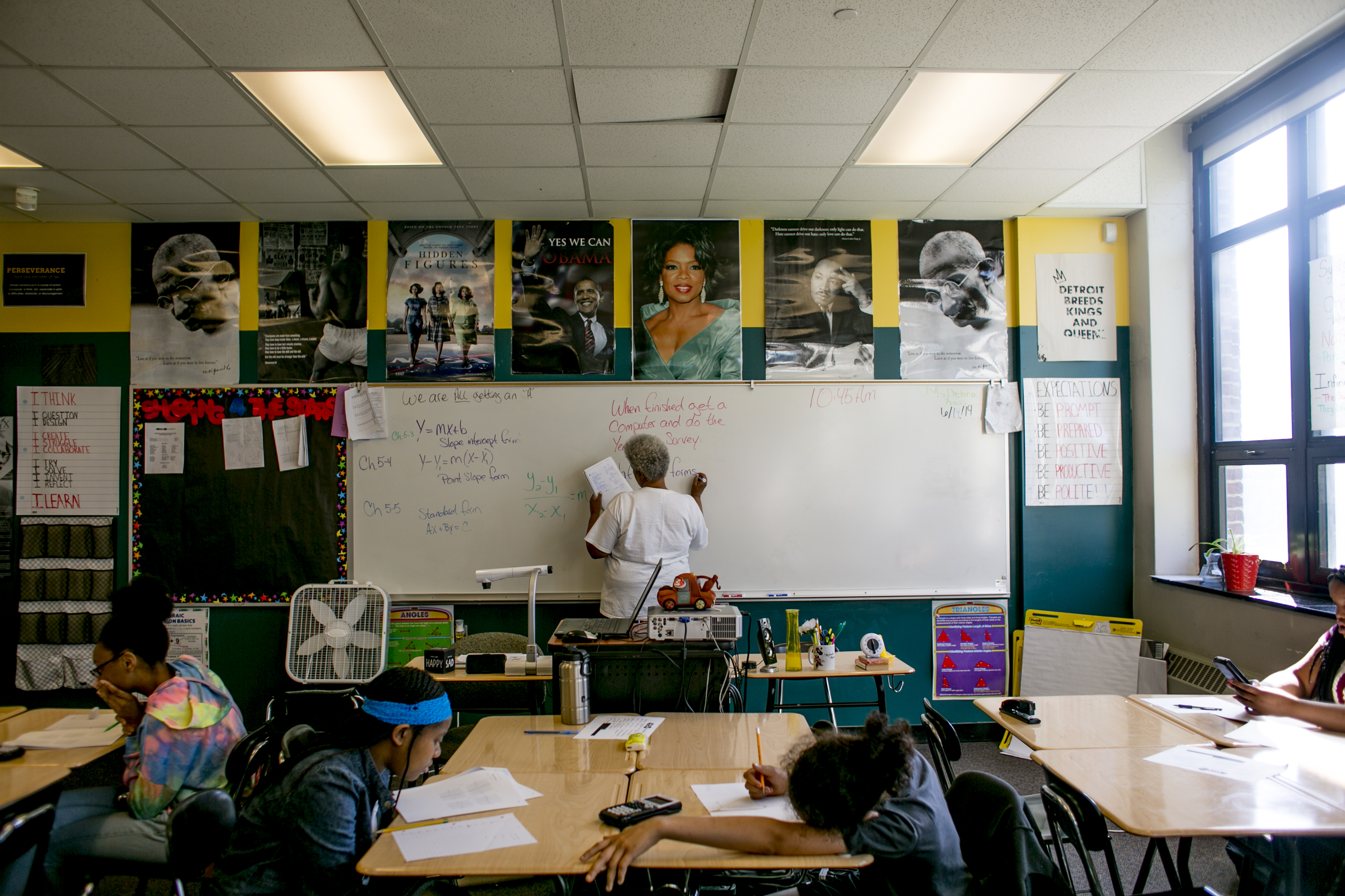 As students work at their desks, a teacher writes on a board in a math class at Southeastern High School in Detroit, MI. Photo by Anthony Lanzilote/Chalkbeat; Taken June, 2019
