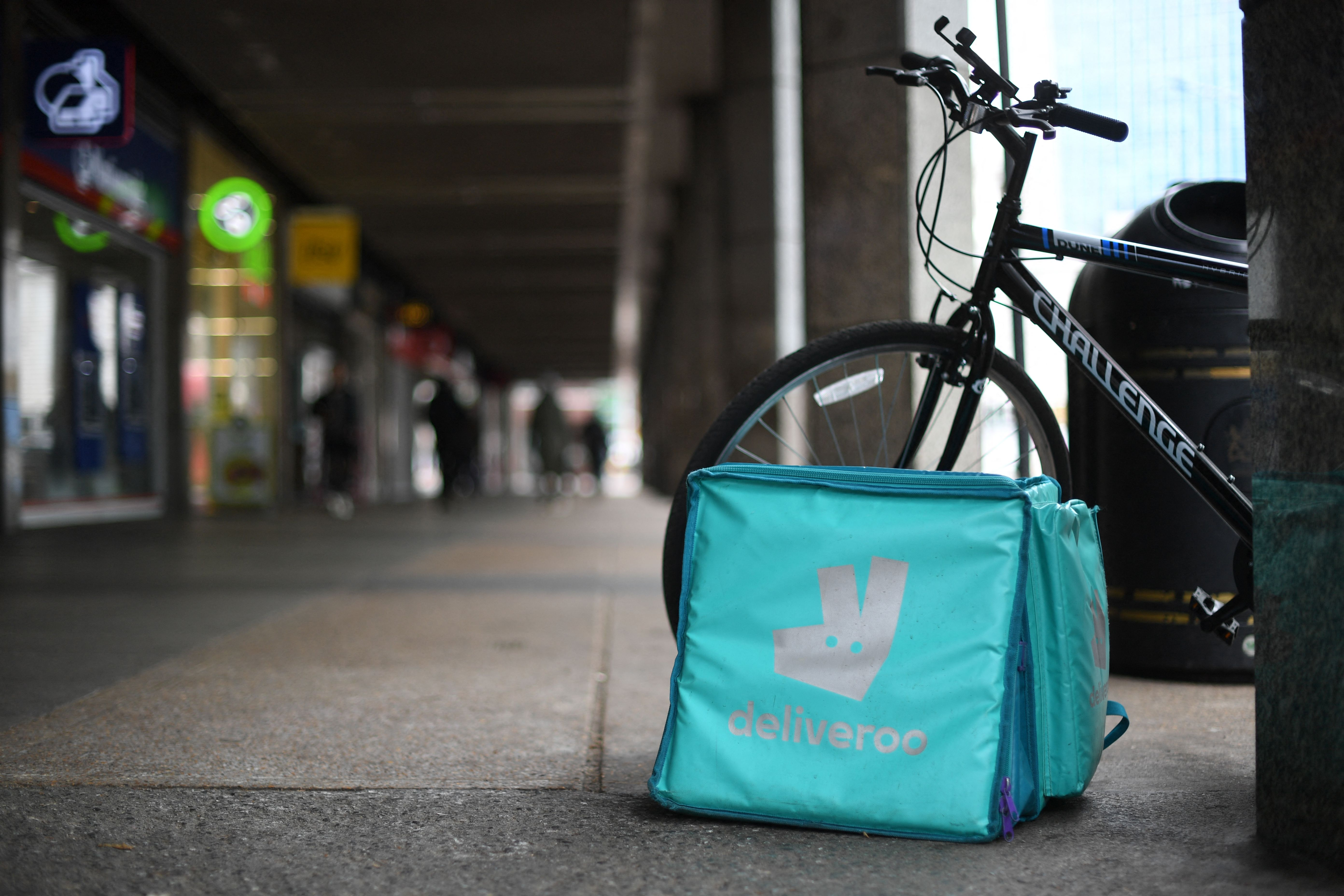 A cerulean Deliveroo food delivery bag sits next to a bike on a pavement in London
