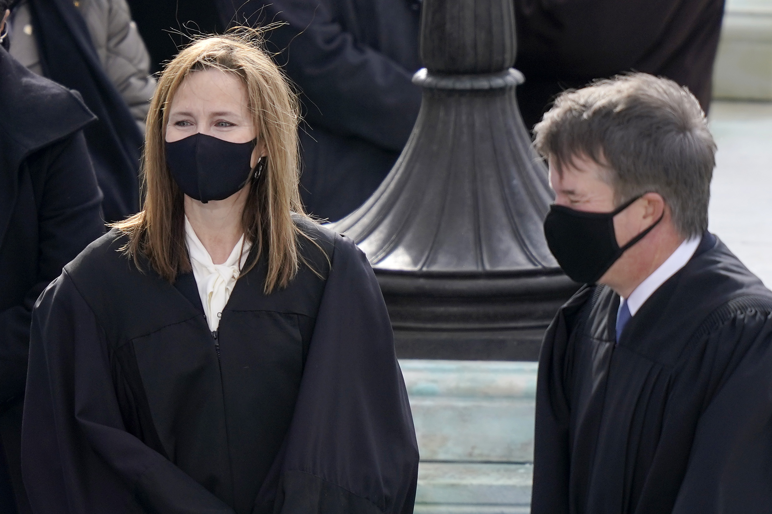 Justices Barrett, left, and Kavanaugh, in black judicial robes and face masks, stand outdoors.