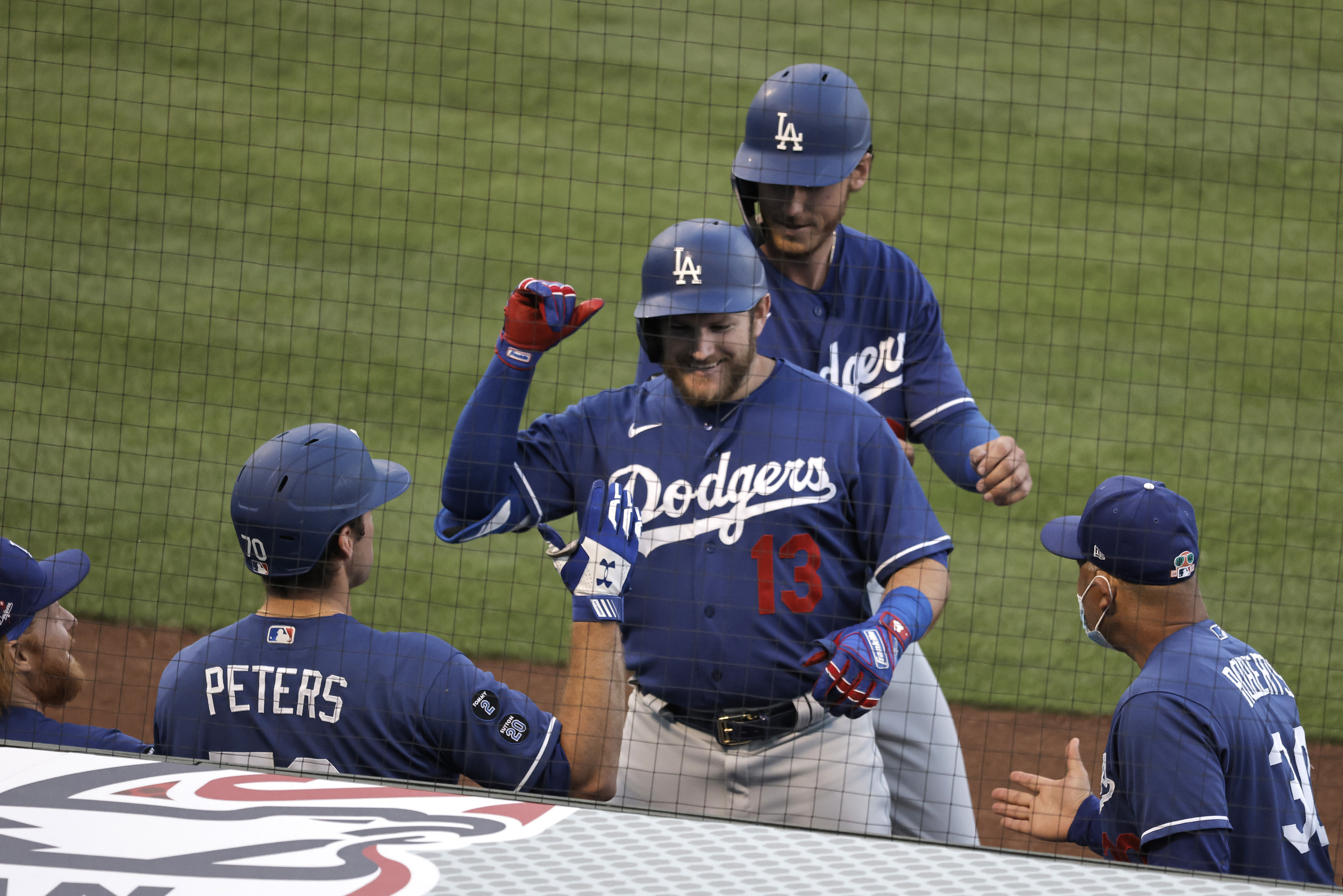 Max Muncy #13 of the Los Angeles Dodgers celebrates his two-run home run with teammates against the Los Angeles Angels during the second inning of a MLB spring training game on March 28, 2021 in Anaheim, California.