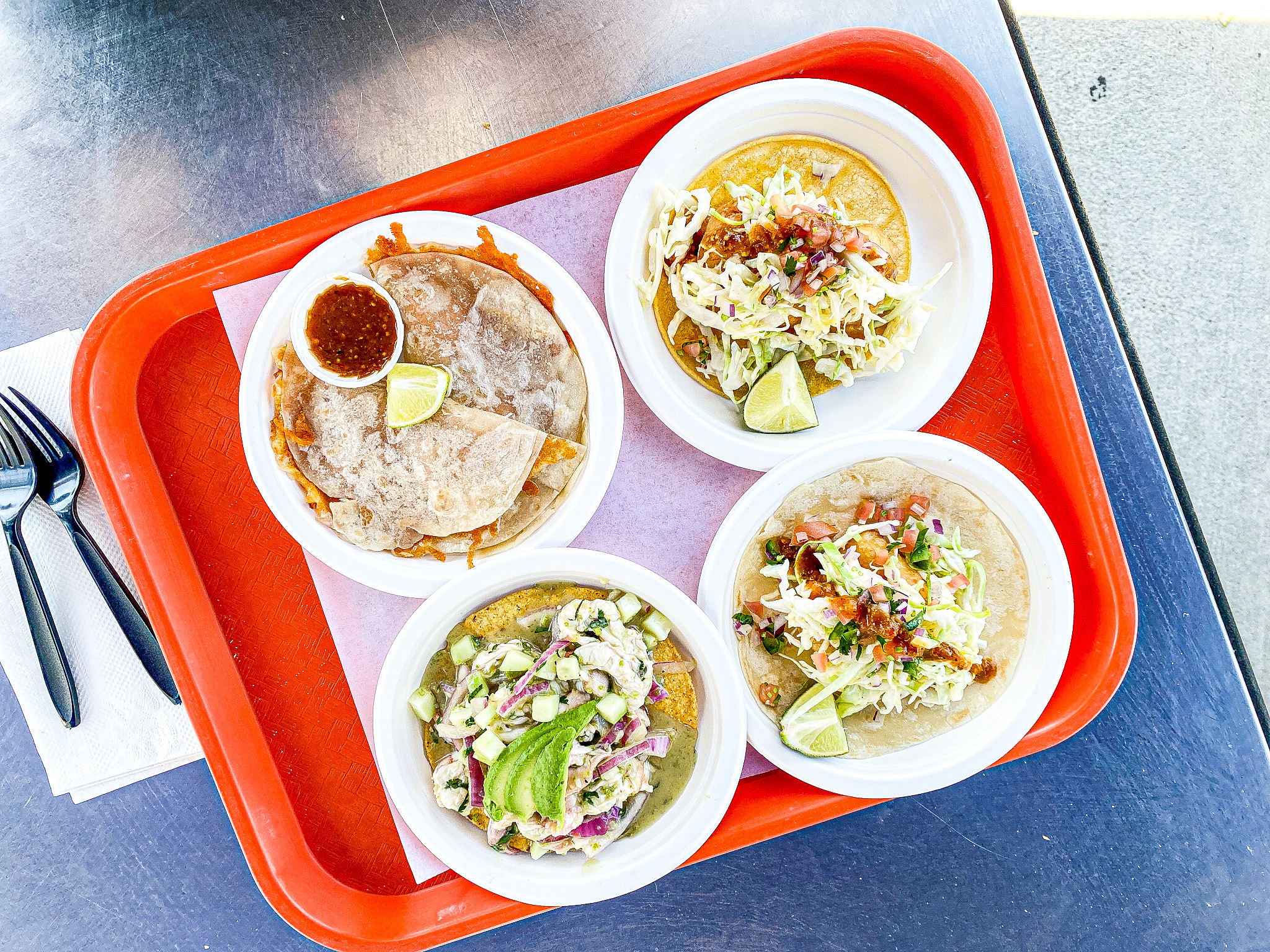 An overhead look at an orange tray filled with different types of seafood, including tacos.