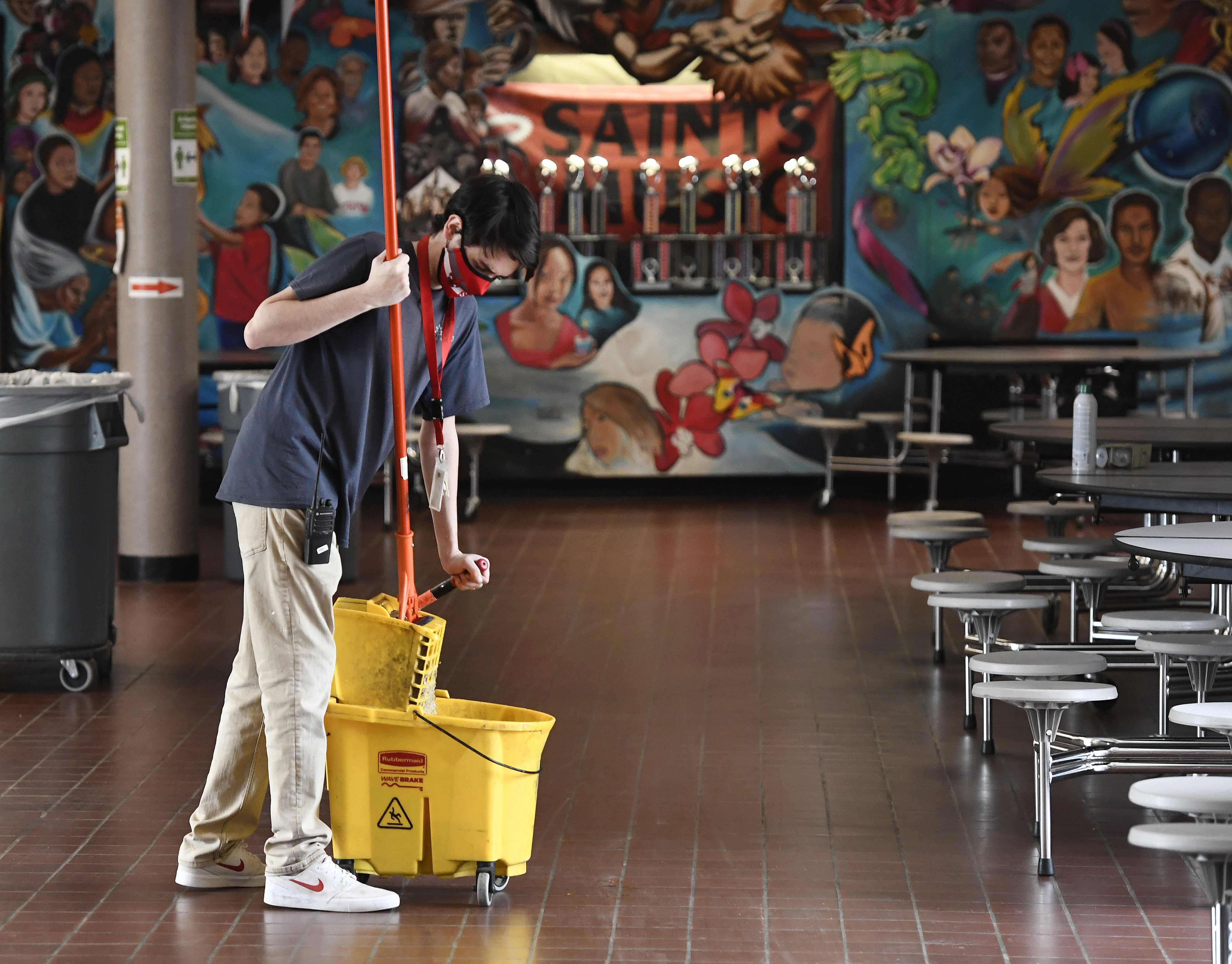 """Custodian wearing mask squeezes a mop into a bucket in a classroom decorated with a colorful full-wall mural saying """"Saints."""""""