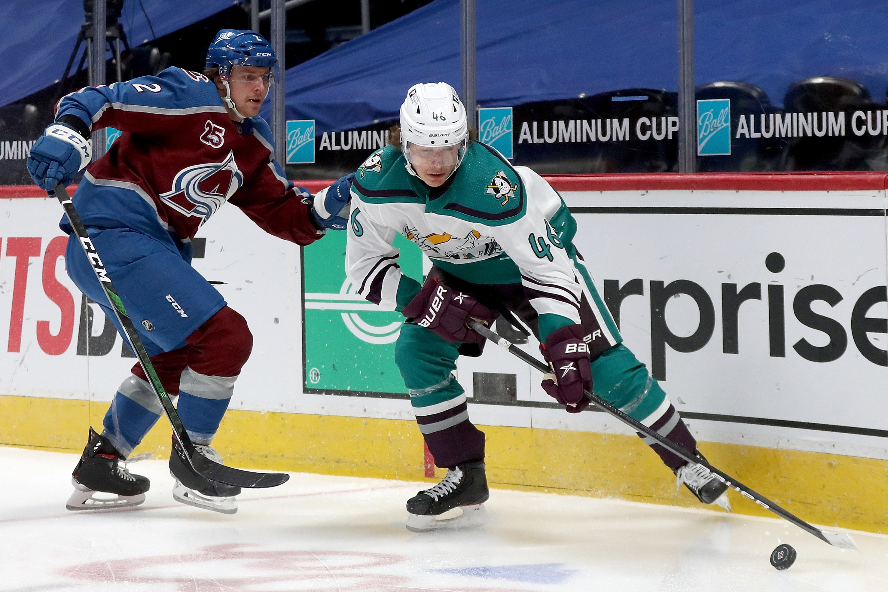 Trevor Zegras #46 of the Anaheim Ducks brings the puck off the boards against Dan Renouf #2 of the Colorado Avalanche in the first period at Ball Arena on March 16, 2021 in Denver, Colorado.