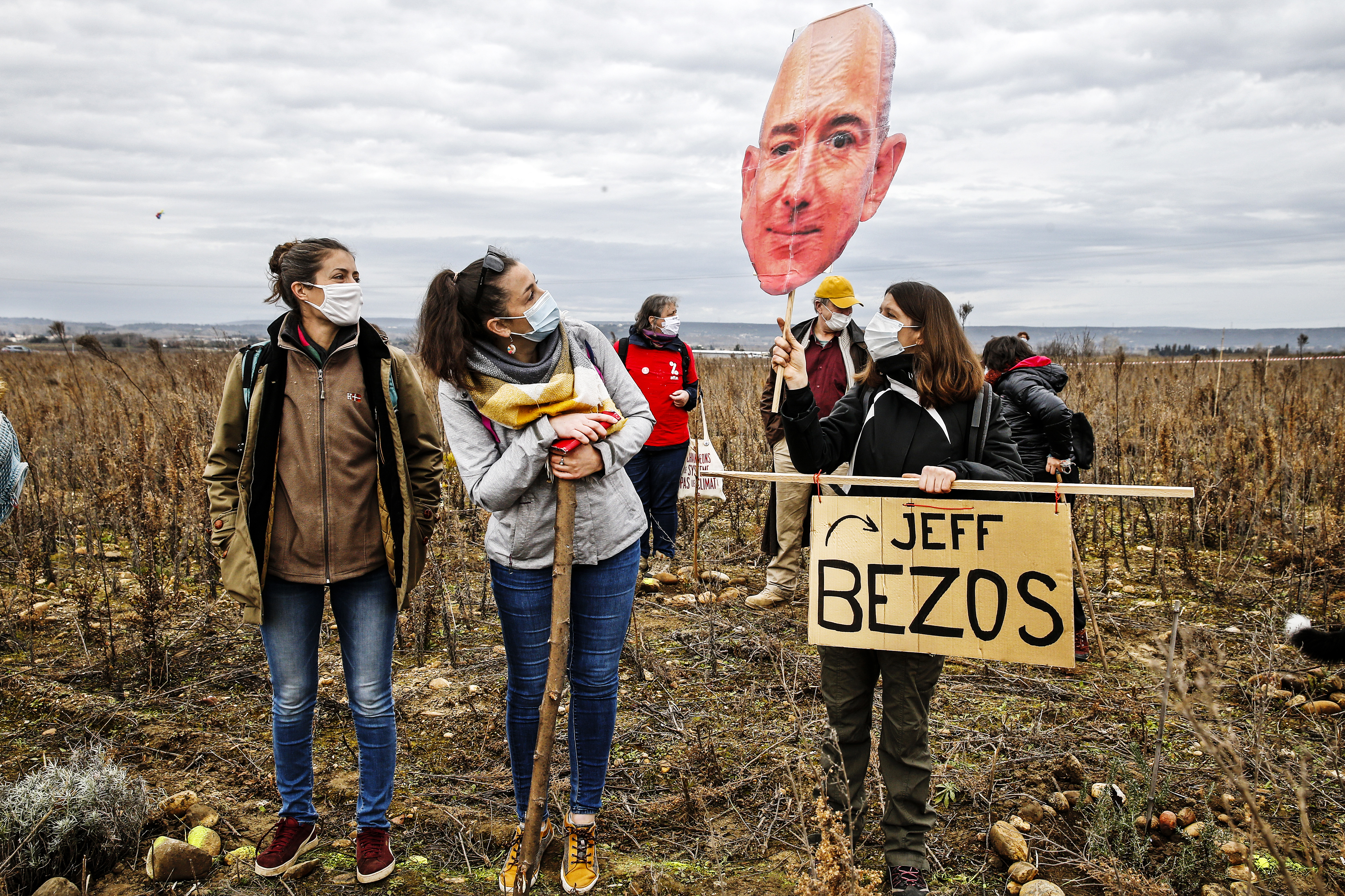 """Protesters standing in a scrubby field and holding a cutout of Jeff Bezos's face along with a sign saying """"Jeff Bezos."""""""