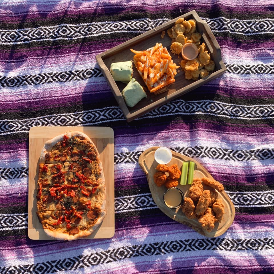 a couple of takeout dishes on a purple woven blanket