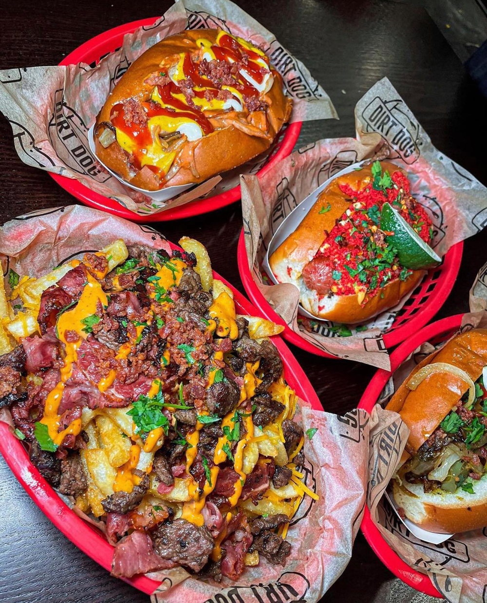 A trio of bacon wrapped hot dogs, plus pastrami, carne asada and bacon bits topped fries, on the popular menu at Dirt Dog.