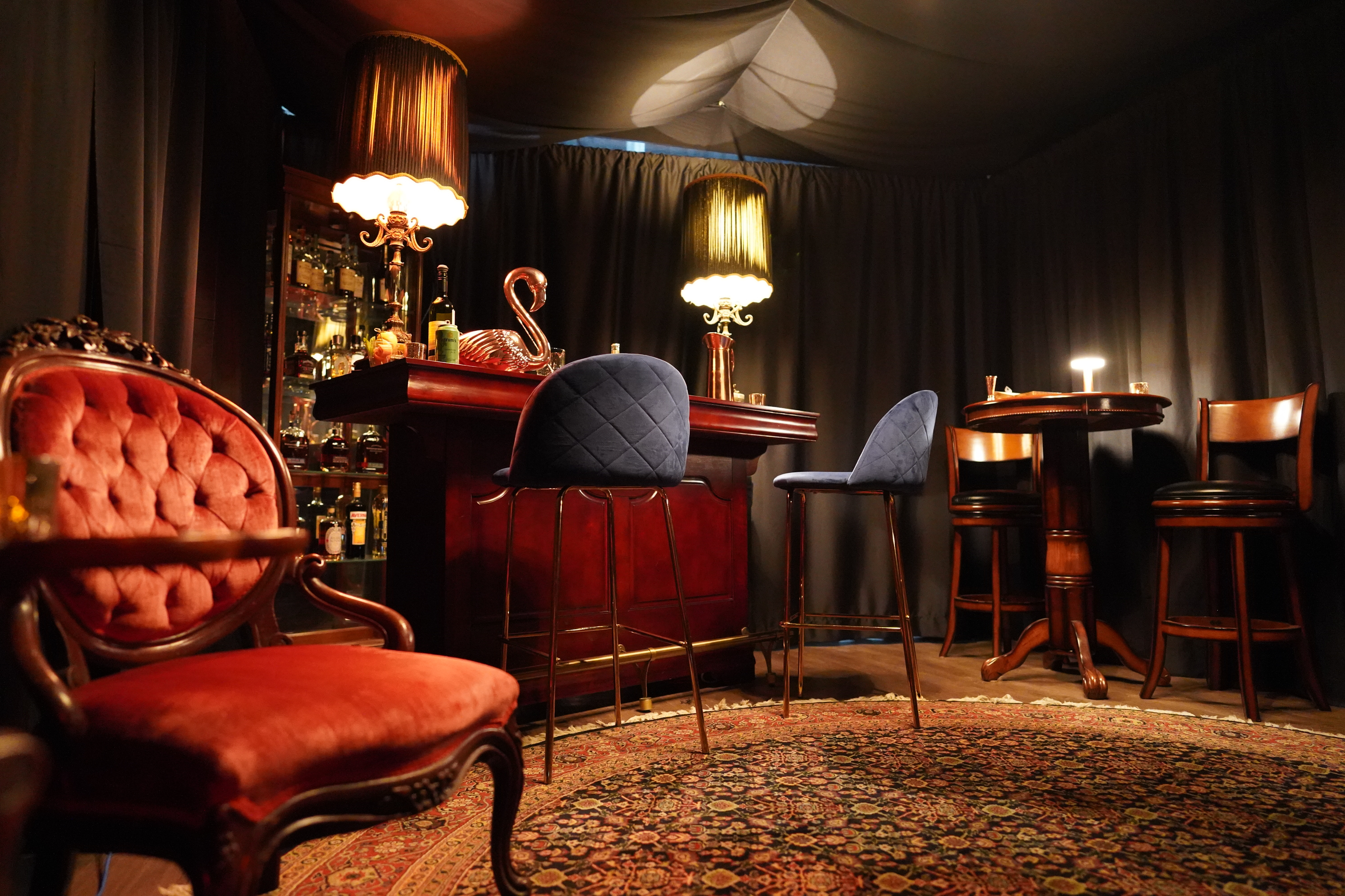 dark bar with red chair in the foreground, two blue velvet chairs in the background