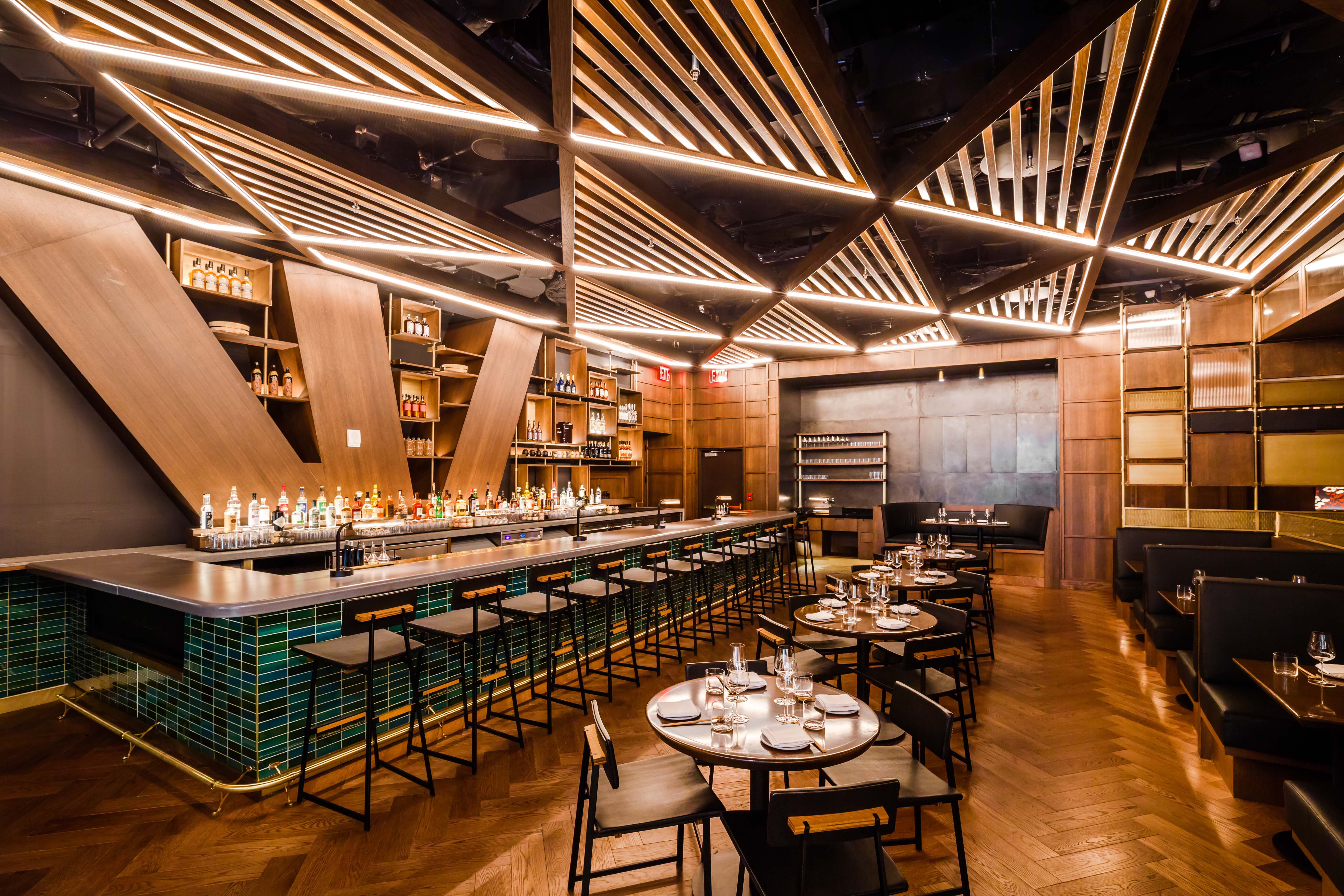 The interior of the Hudson Yards restaurant Kawi with with triangular shaped light panels above a wooden dining room