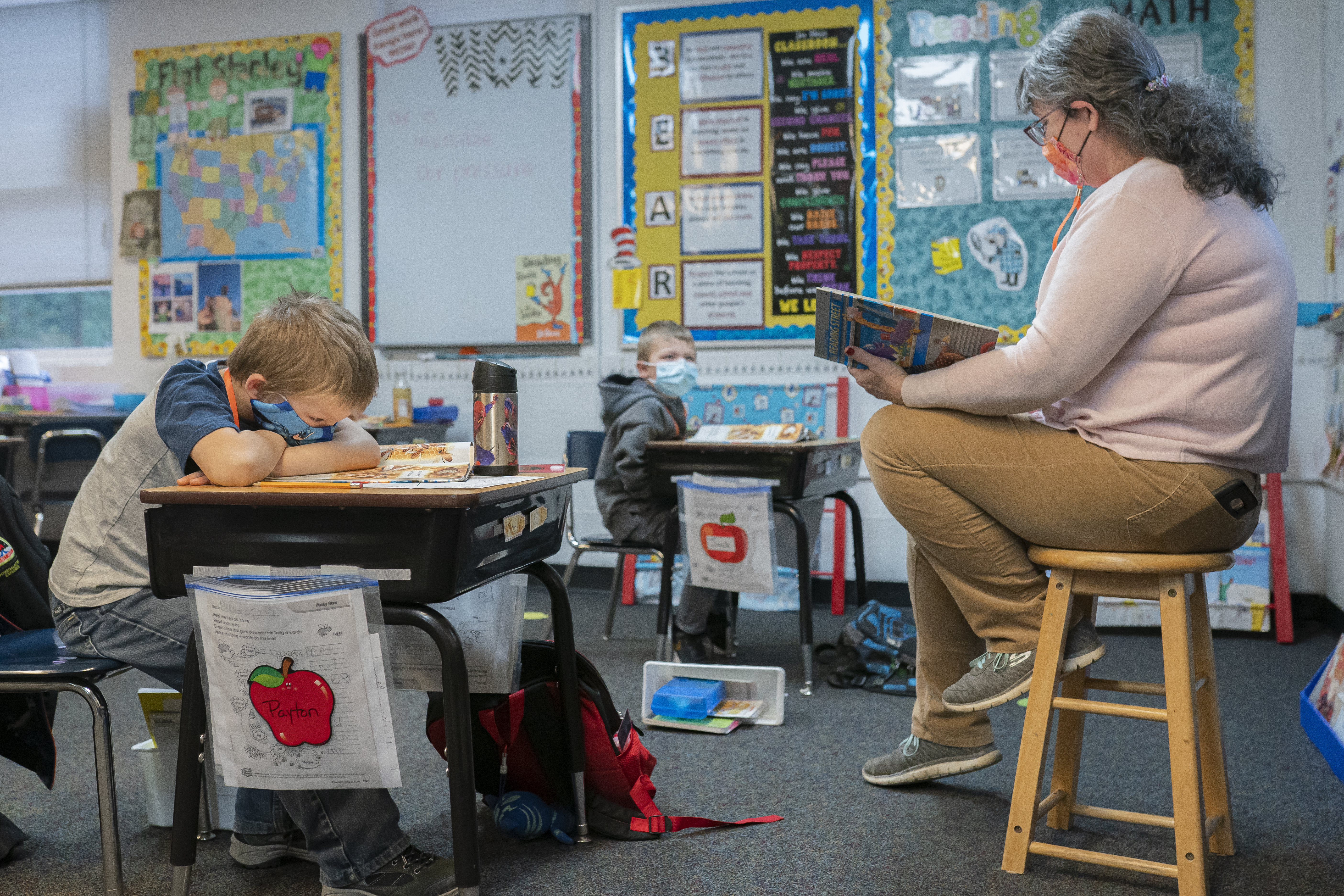 A masked teacher sitting on a stool looks at a book while a masked student, sitting at a desk in front of the teacher and his head resting on his crossed arms, looks at an open book.