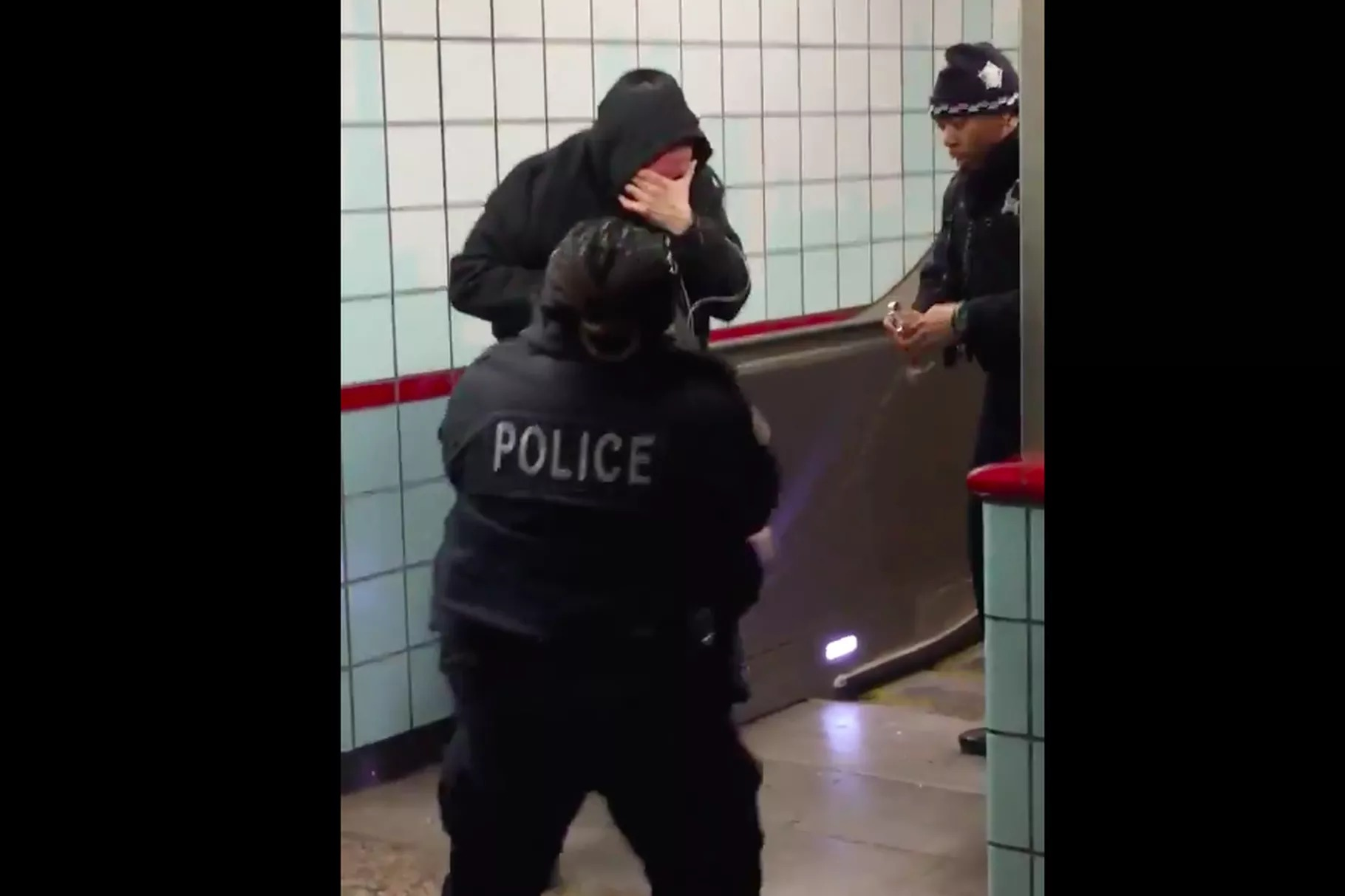 This still image from cellphone video taken in the Grand Red Line station shows Ariel Roman clutching his face moments before a Chicago police officer opened fire on him.