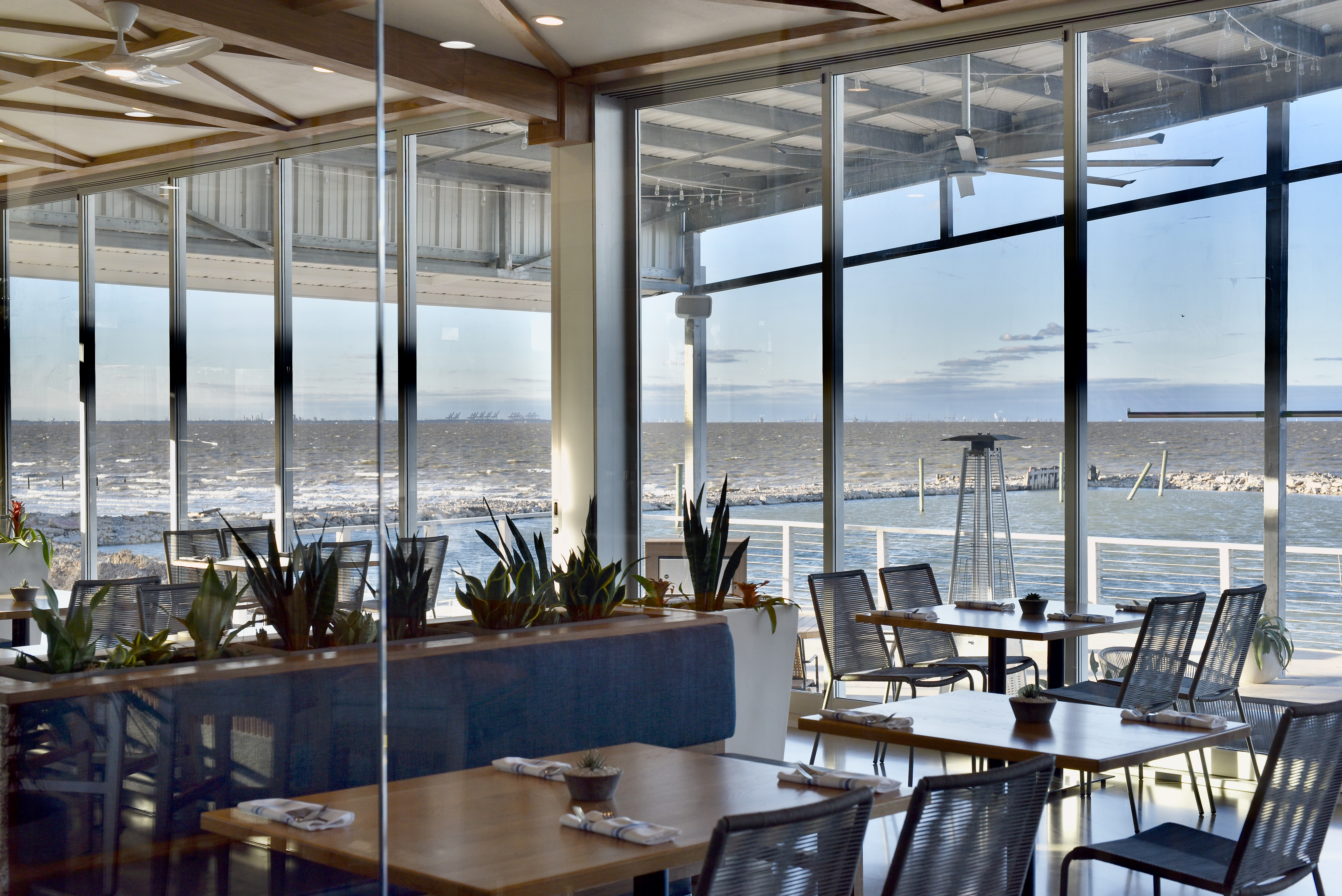 The interior of Pier 6 seafood, overlooking the San Leon waterfront through large windows