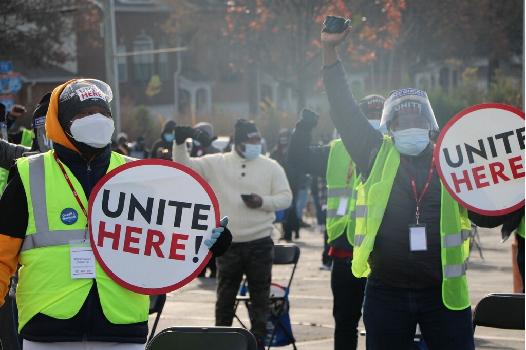 A crowd of union advocates for Unite Here Local 23 in support of Georgia hospitality workers rally for Jon Ossoff and Raphael Warnock in the fall of 2020 with fists raised in the air for solidarity. Two masked people stand with signs reading Unite Here! in neon vests