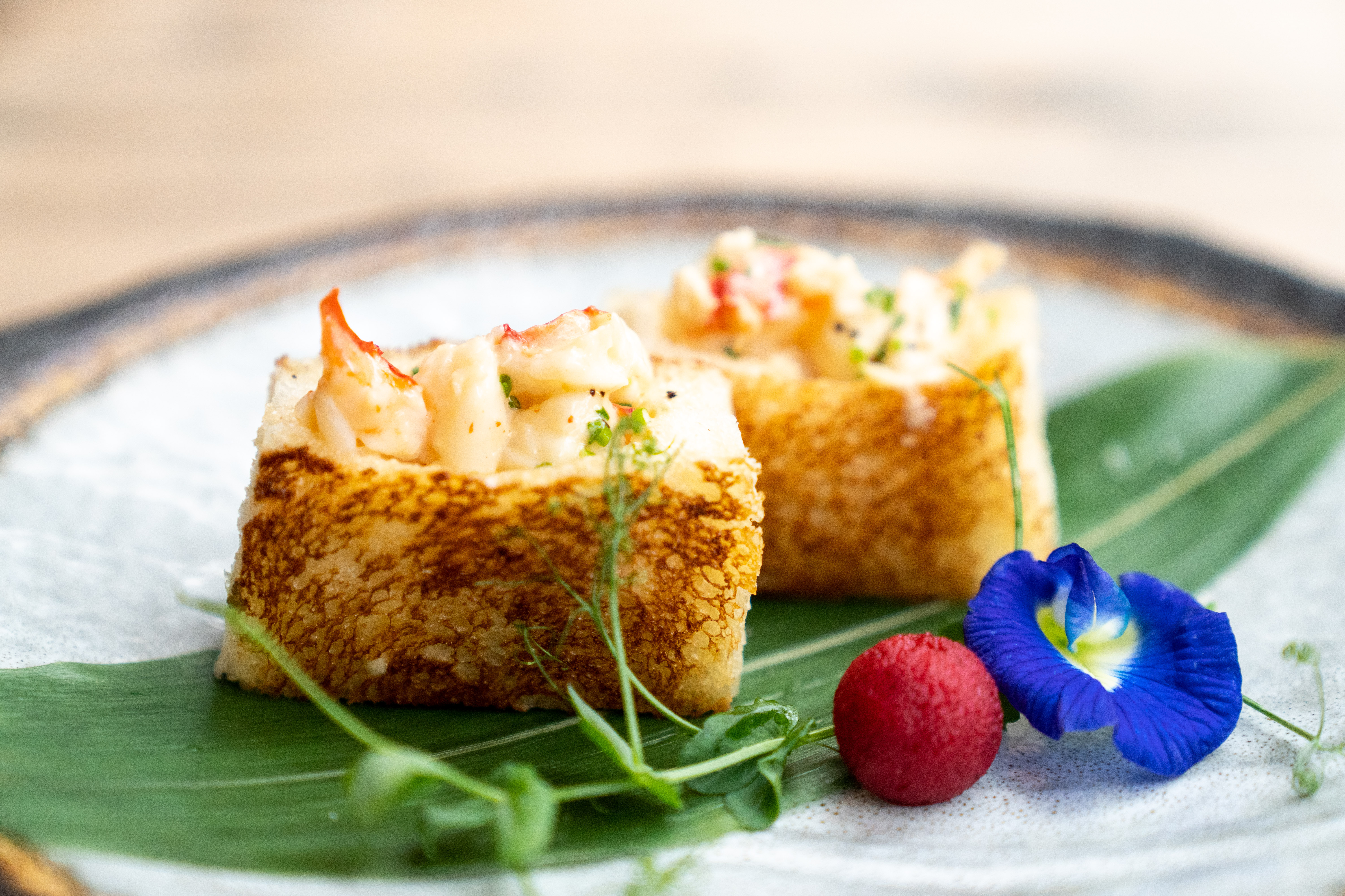 a japanese milk bread sandwich topped with lobster and served alongside greens and ornamental flowers