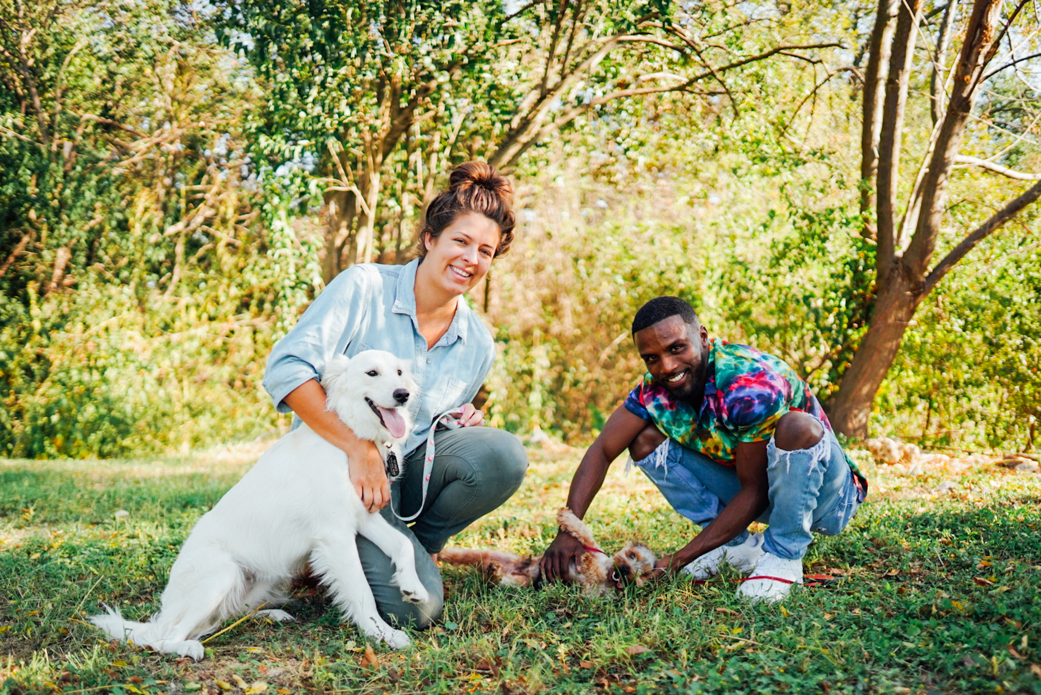 Kati Luedecke and Lamar Bowman in a park with a dog.