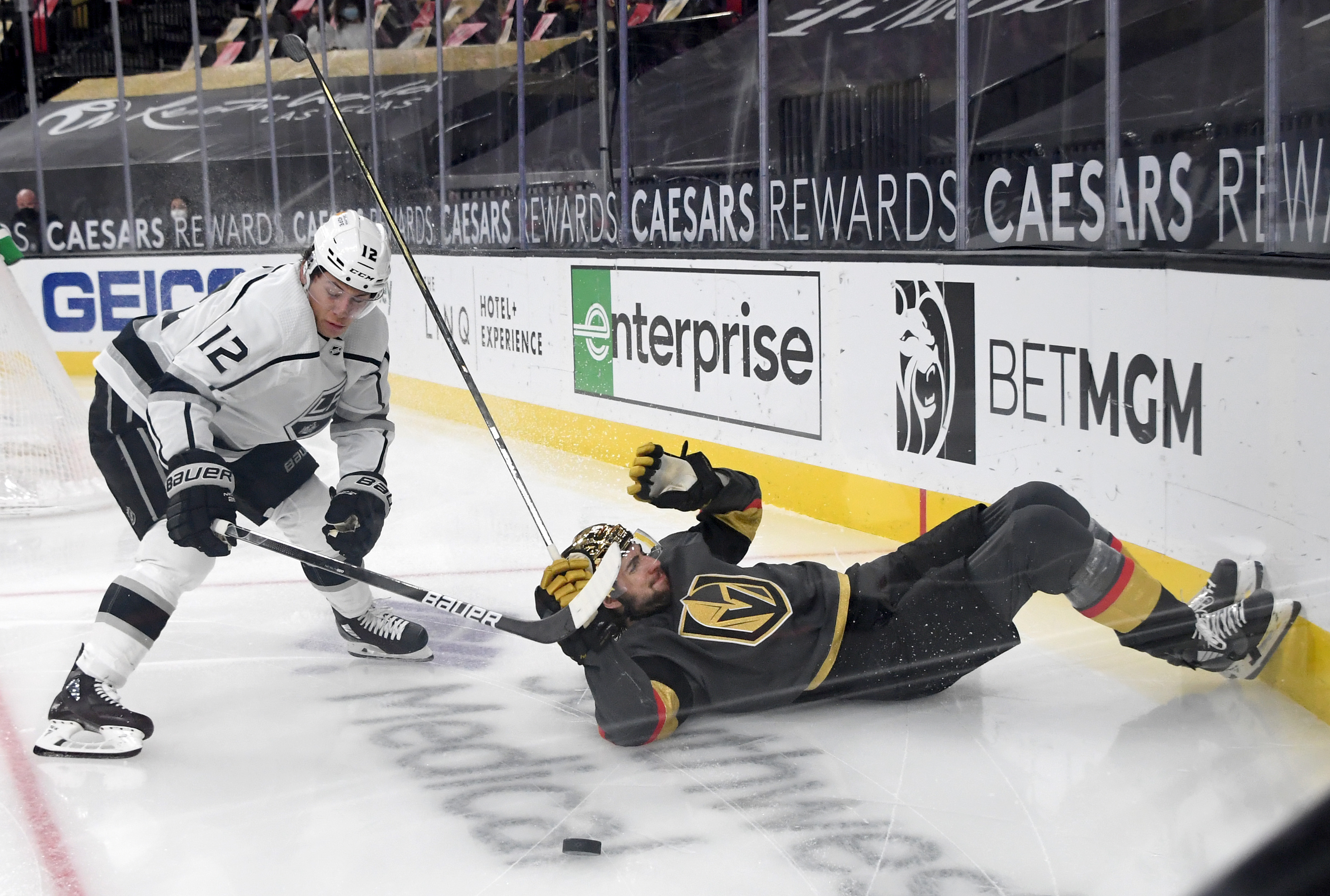Nicolas Hague #14 of the Vegas Golden Knights falls as he and Trevor Moore #12 of the Los Angeles Kings go after the puck in the third period of their game at T-Mobile Arena on March 29, 2021 in Las Vegas, Nevada. The Golden Knights defeated the Kings 4-1.
