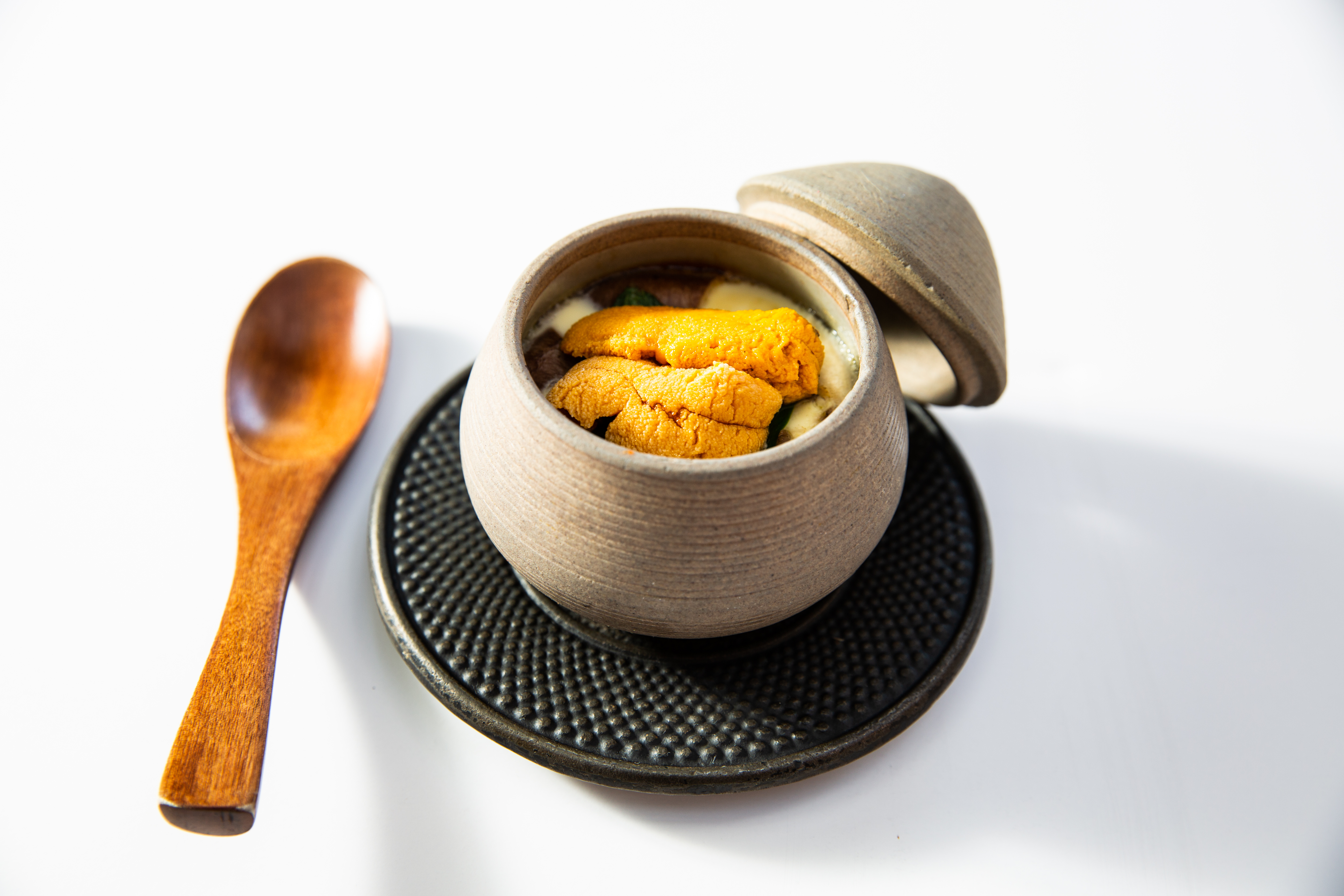 egg and uni custard in a clay pot with a wooden spoon