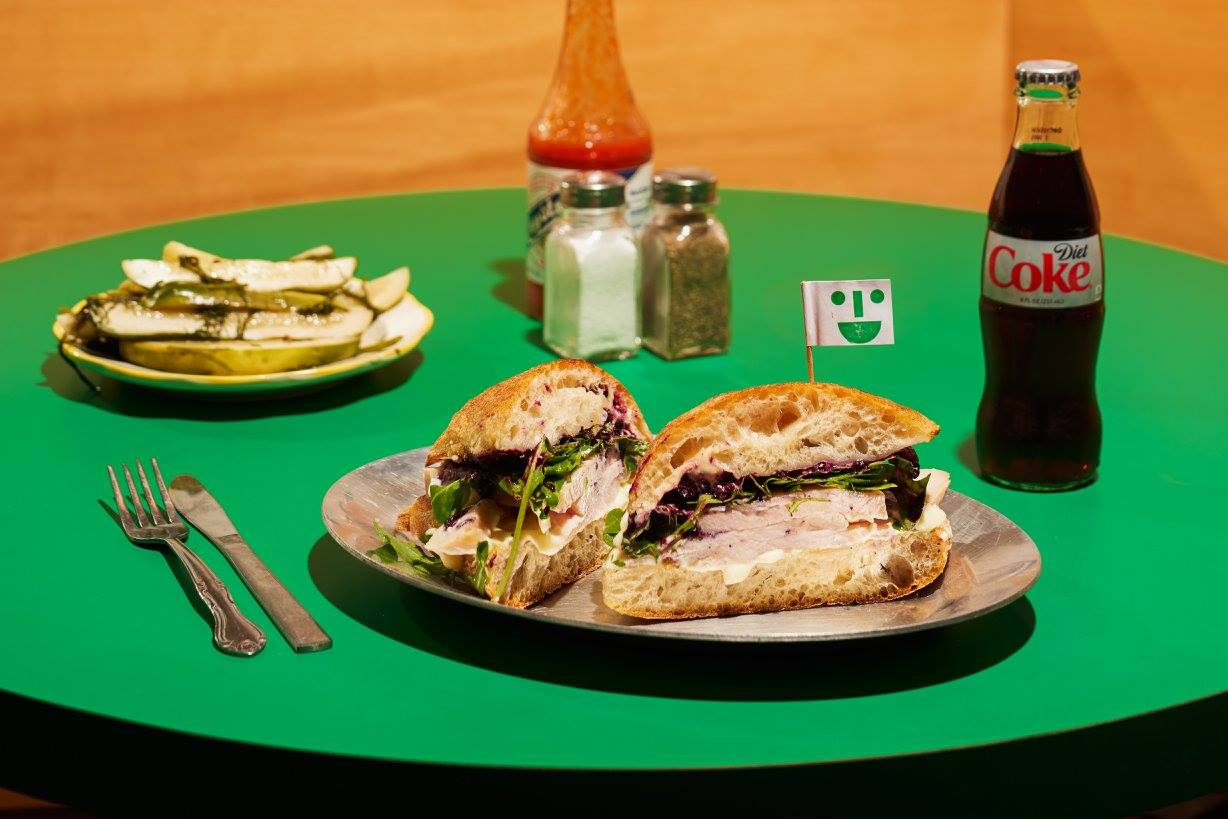 a green table with middle child turkey sandwich, pickles, a coke and place settings