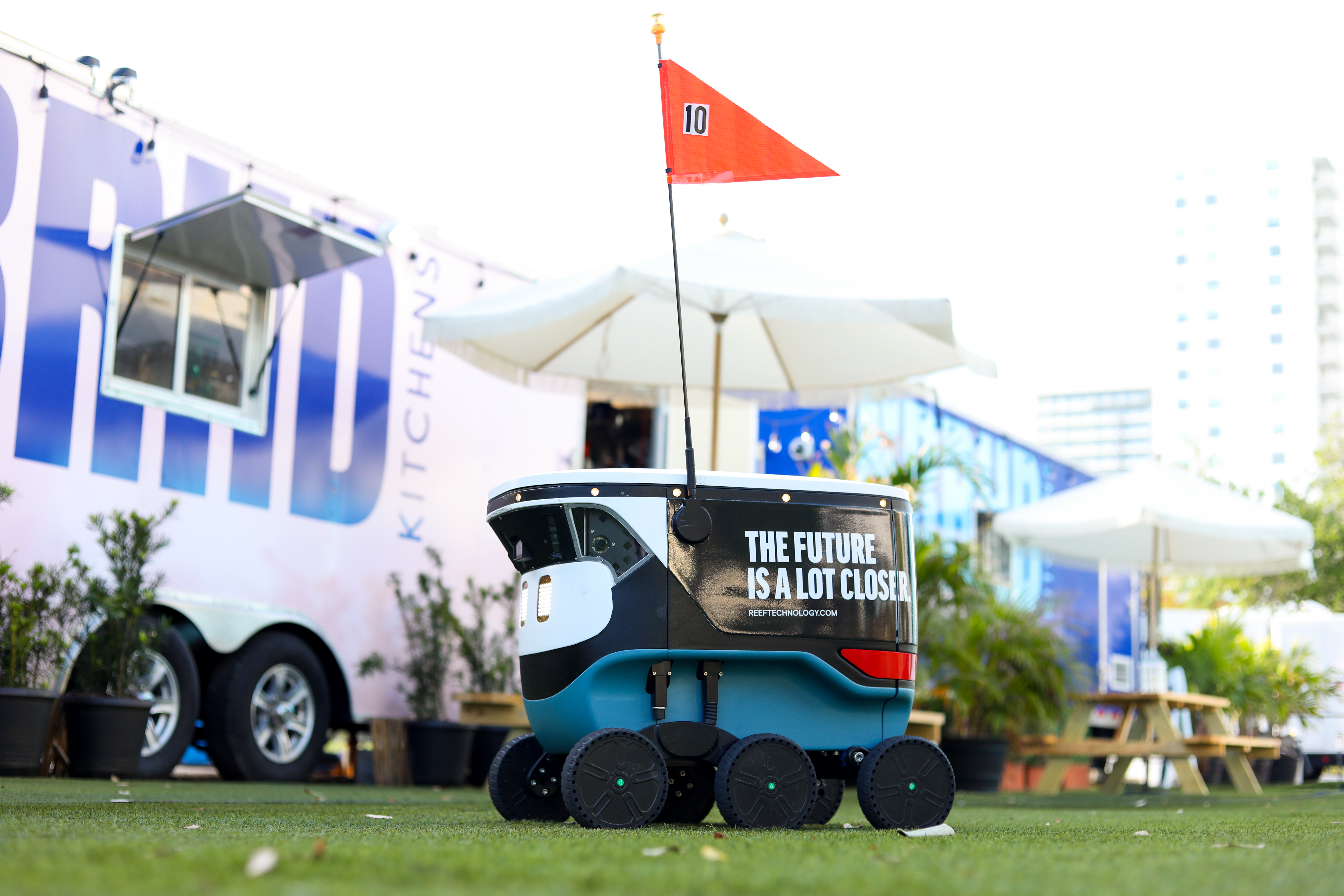 robot on green lawn with trailer in the back on grass