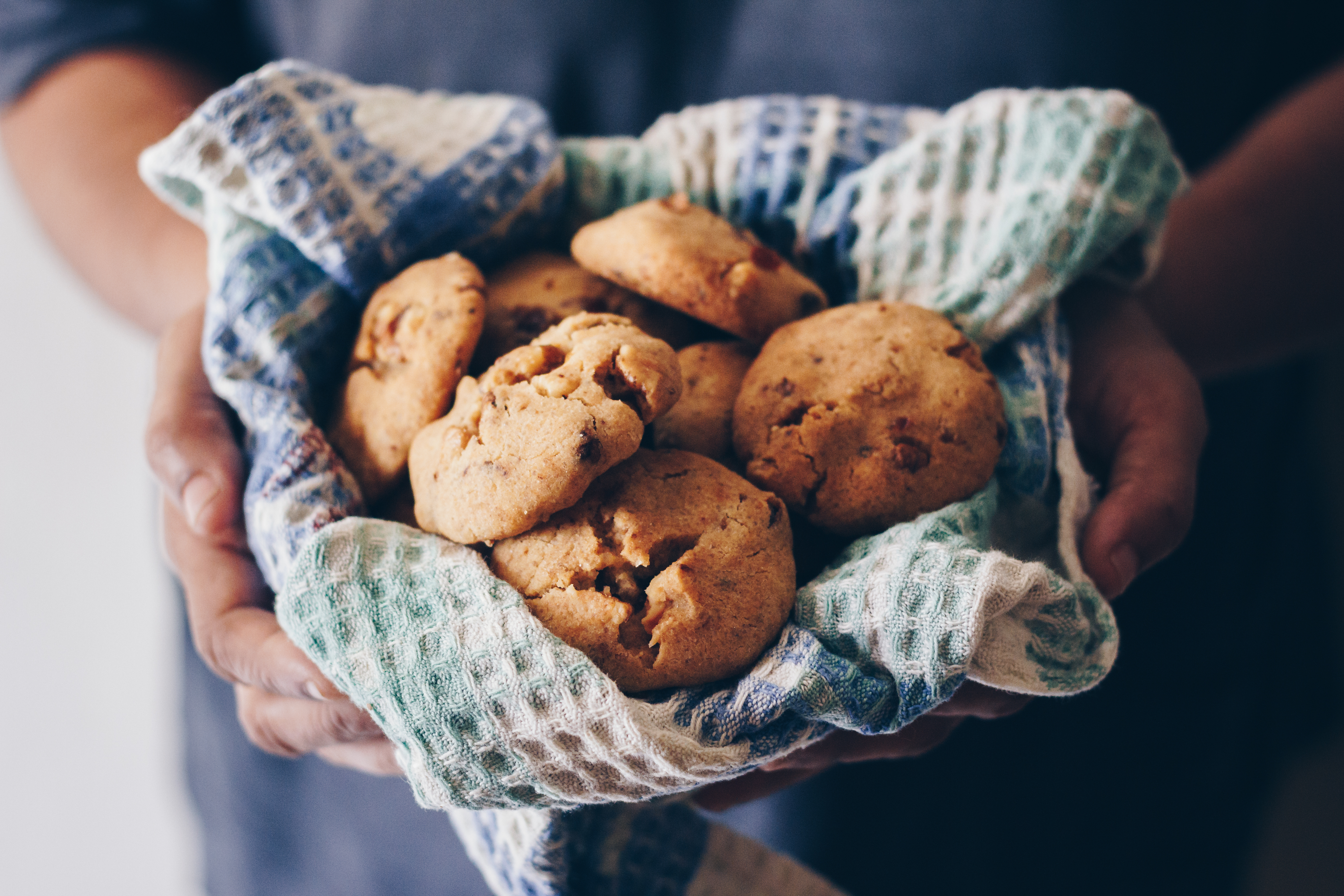 Two hands hold a basket of cookies. The basket is lined with a white and blue checkered cloth.