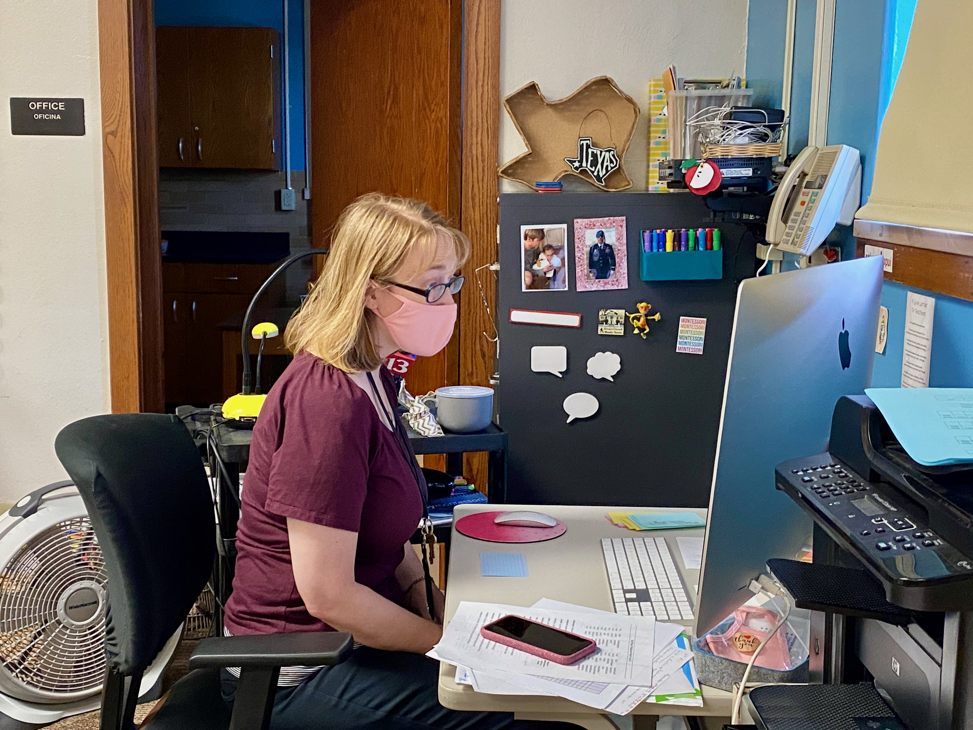 A teacher wearing a mask works with students remotely at a computer in her classroom.
