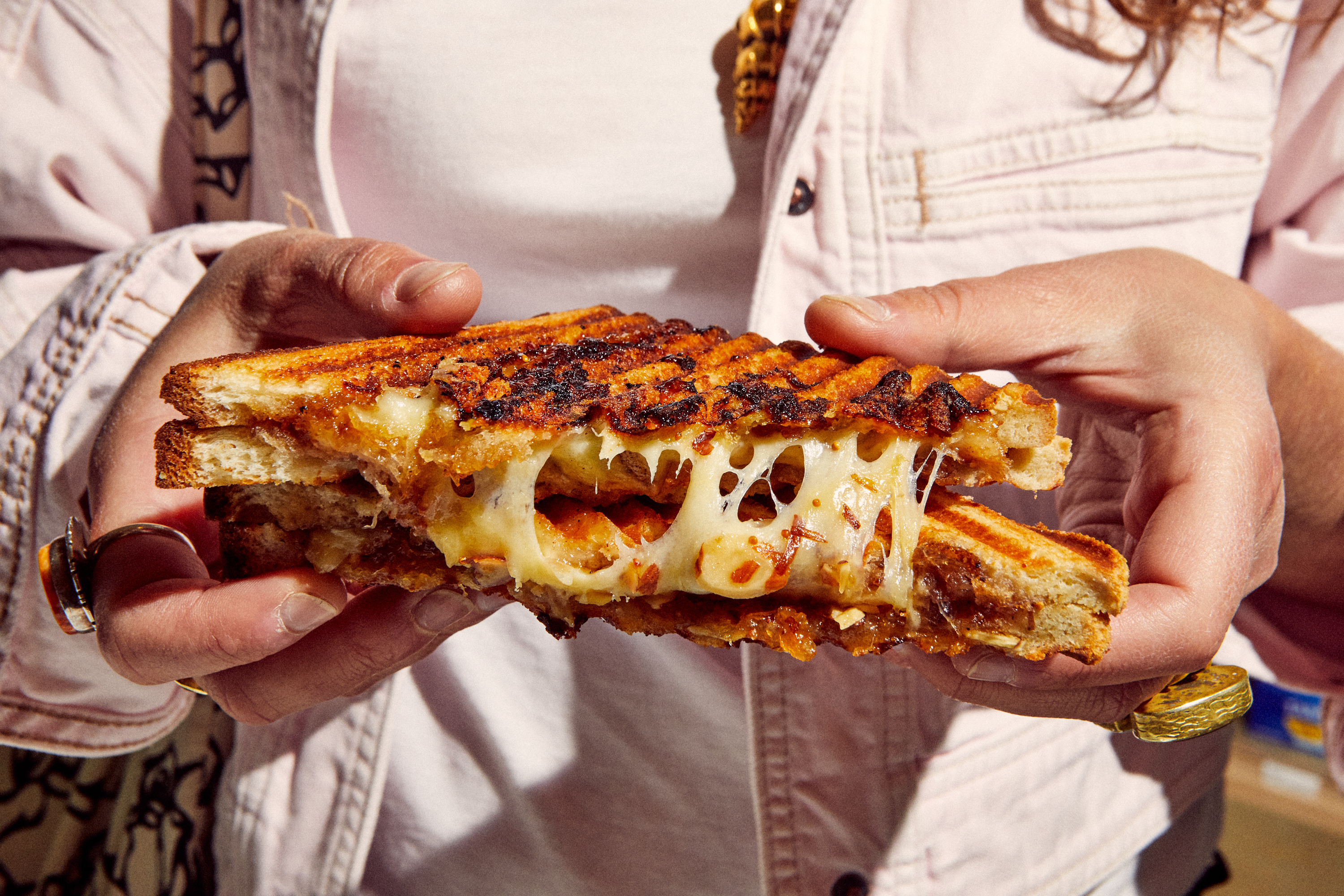 Gooey grilled cheese held by someone in an off-white shirt