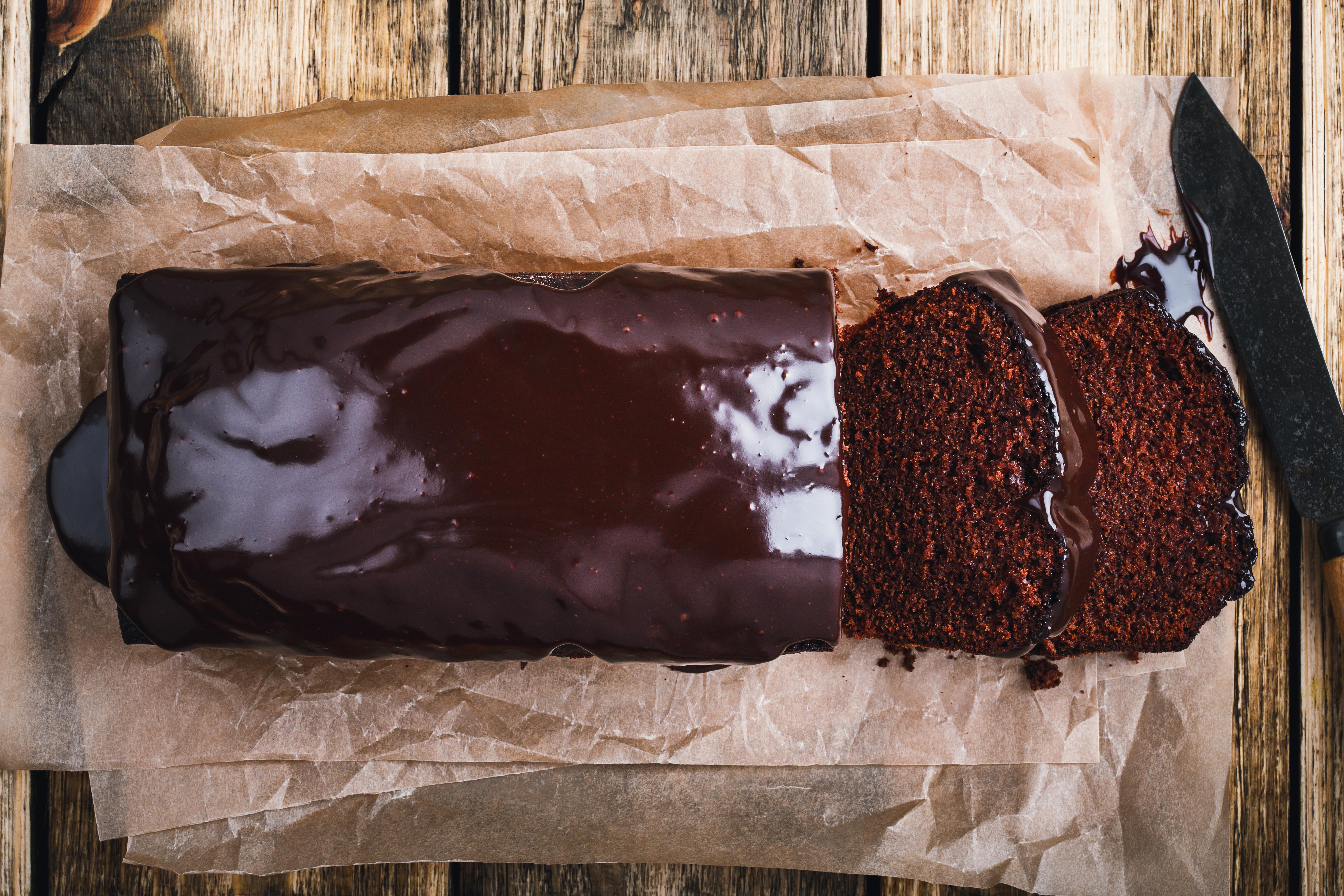 上方的图像上釉巧克力面包蛋糕在木板上,两切显示蛋糕的内部。