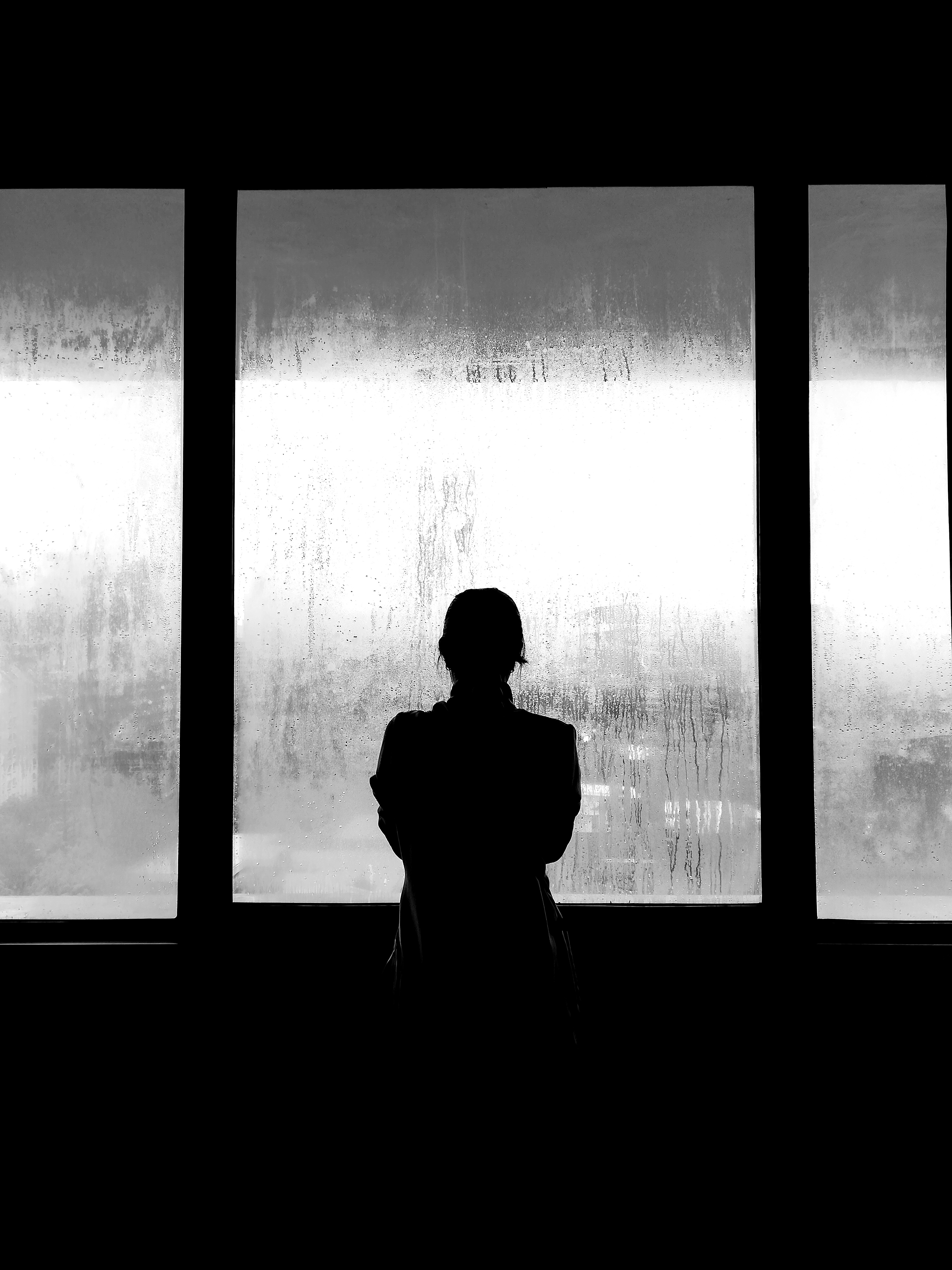 A young woman standing with her back to the camera, looking through frosted glass.