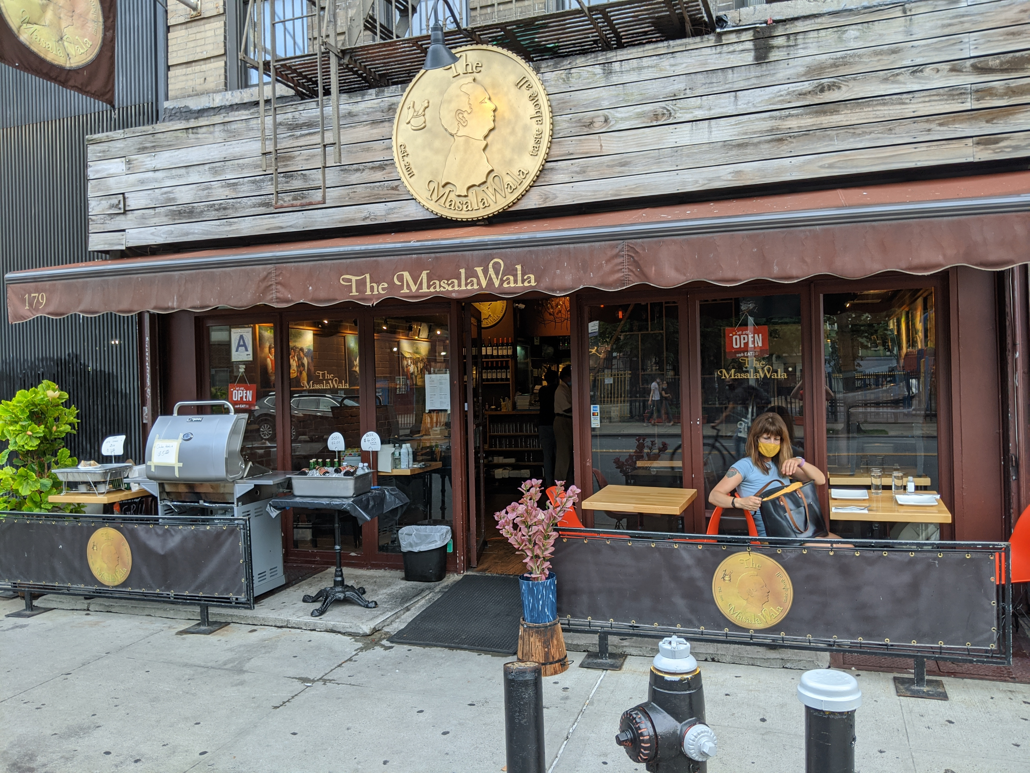 A broad brown storefront with a single customer sitting at a table with a mask.