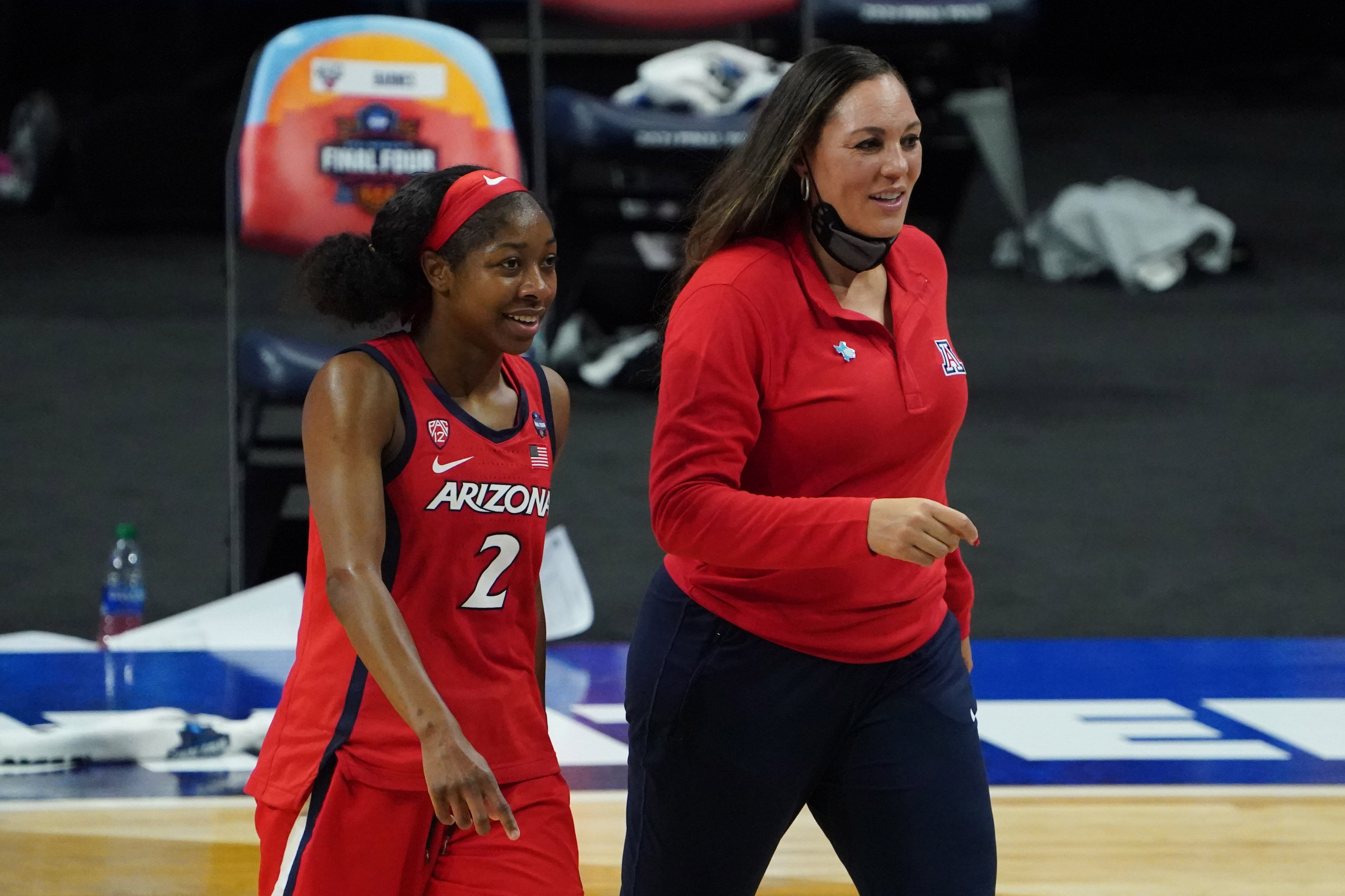 Arizona Wildcats guard Aari McDonald and Arizona Wildcats head coach Adia Barnes walk off the court after defeating the UConn Huskies in the national semifinals of the women's Final Four of the 2021 NCAA Tournament at Alamodome.