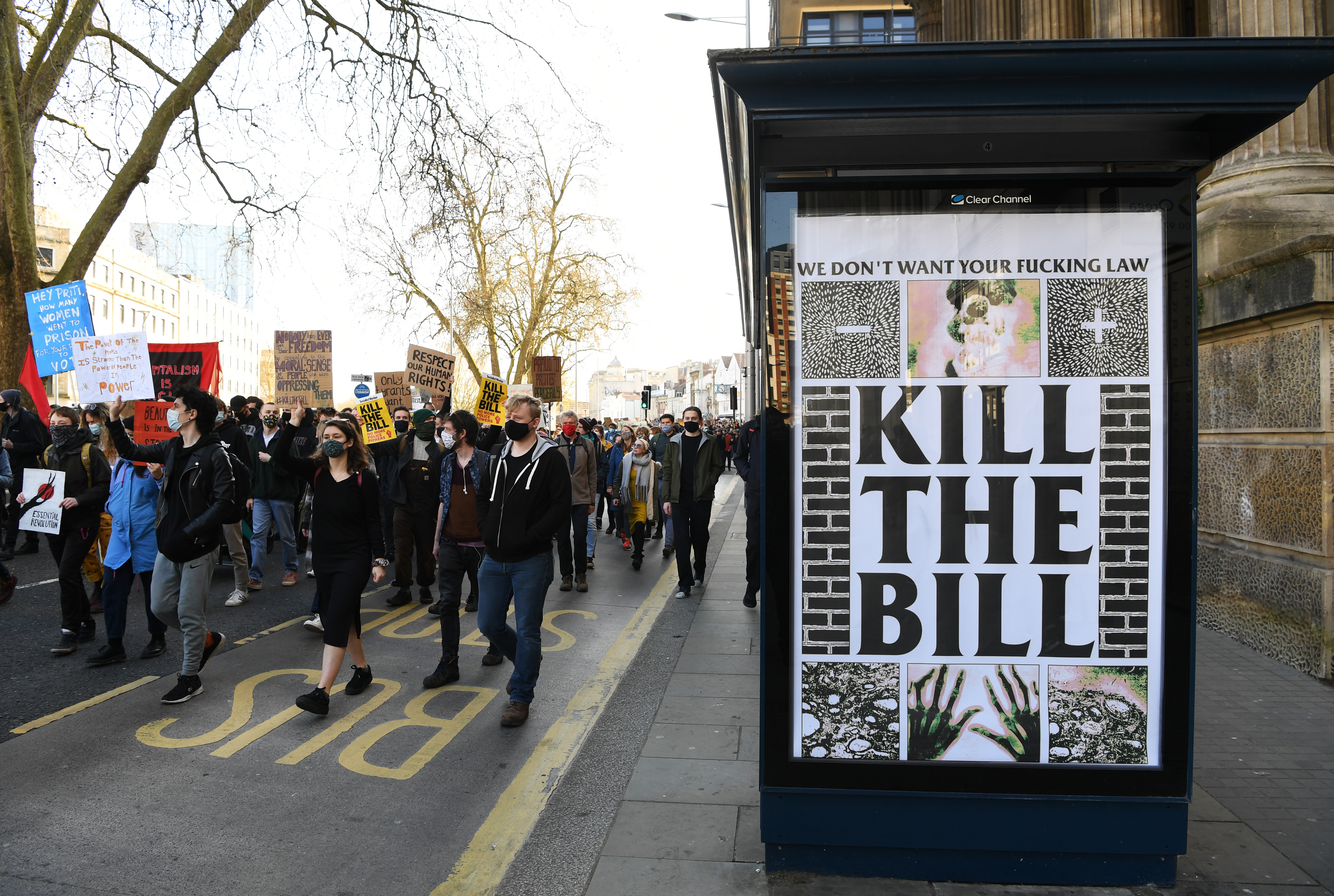 """A crowd of protesters carrying signs march down a street, with a large poster reading """"Kill The Bill"""" nearby."""