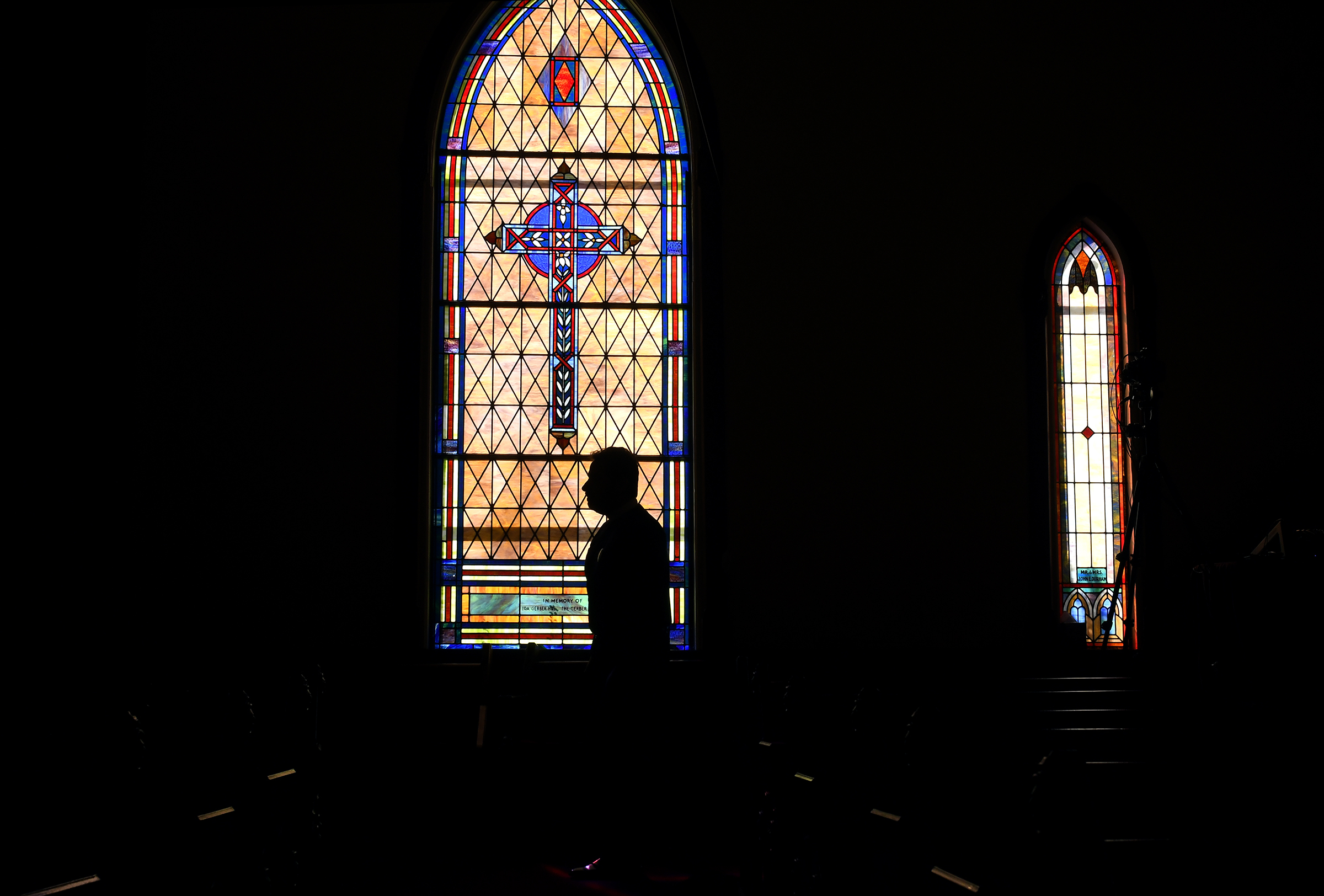 The Rev. Salvatore Sapienza is silhouetted by the stained glass inside the Douglas Congregational United Church of Christ in the village of Douglas, Mich., on Tuesday Oct. 13, 2020.