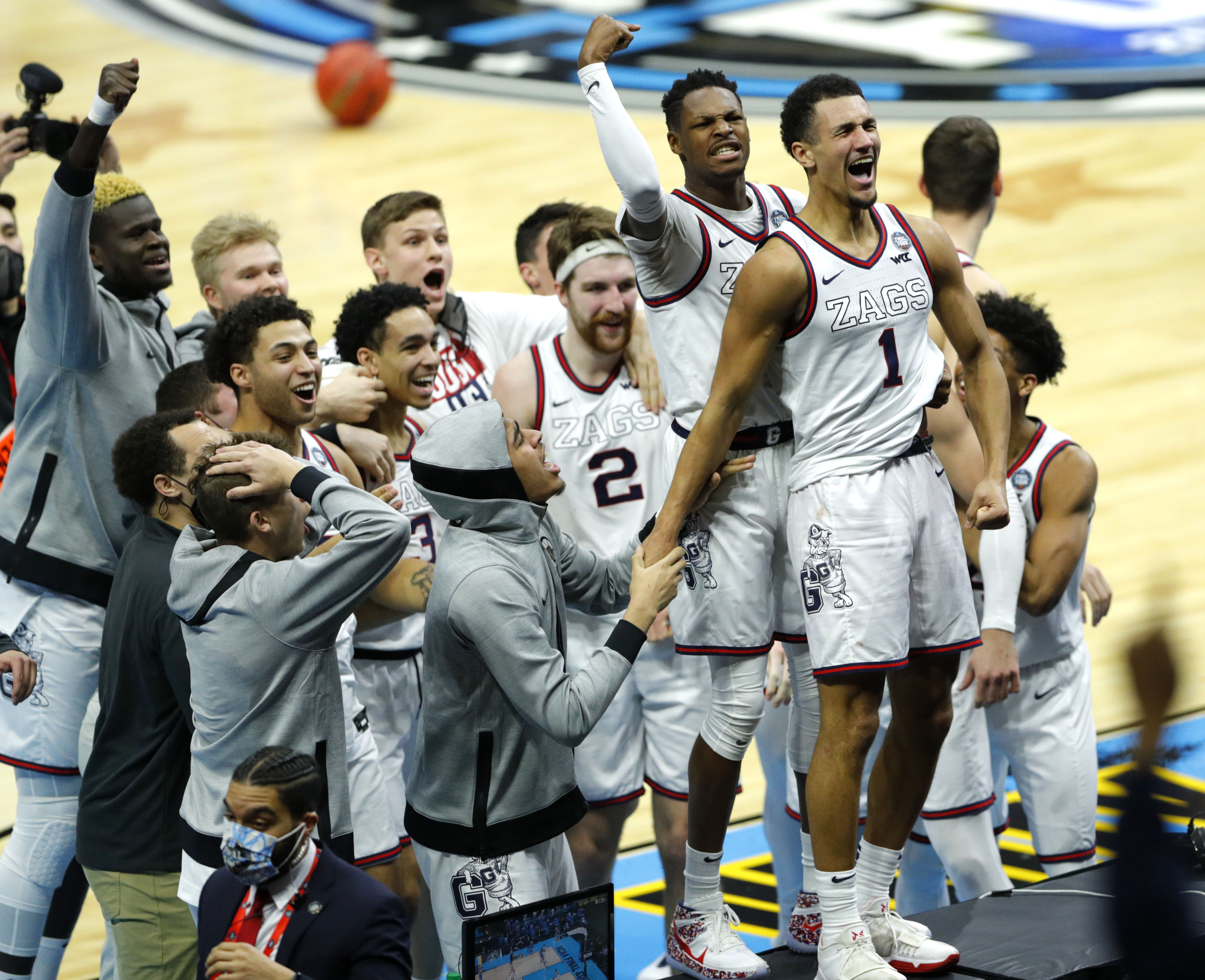 Gonzaga Bulldogs guard Jalen Suggs (1) leaps on a sideline table to celebrate after sinking a buzzer beater three-pointer to defeat UCLA in overtime during the semifinals of the Final Four of the 2021 NCAA Tournament on Saturday, April 3, 2021, at Lucas Oil Stadium in Indianapolis, Ind.