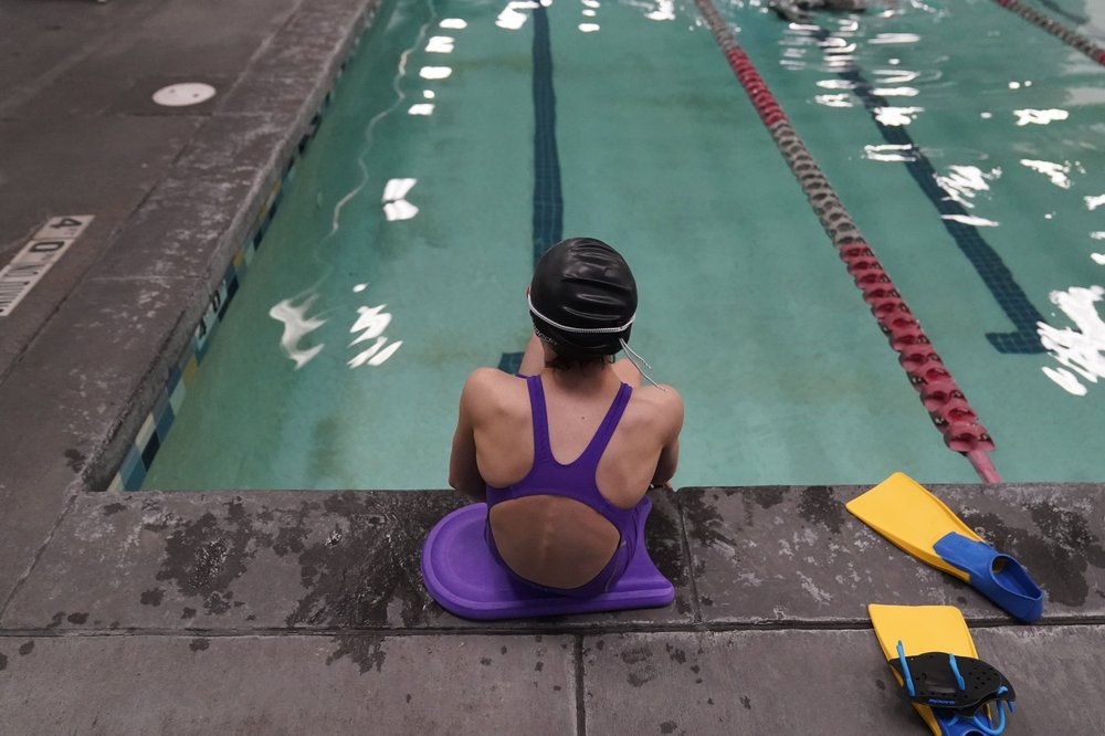 A trans girl wearing a girls bathing suit sits on the edge of a swimming pool in Utah.