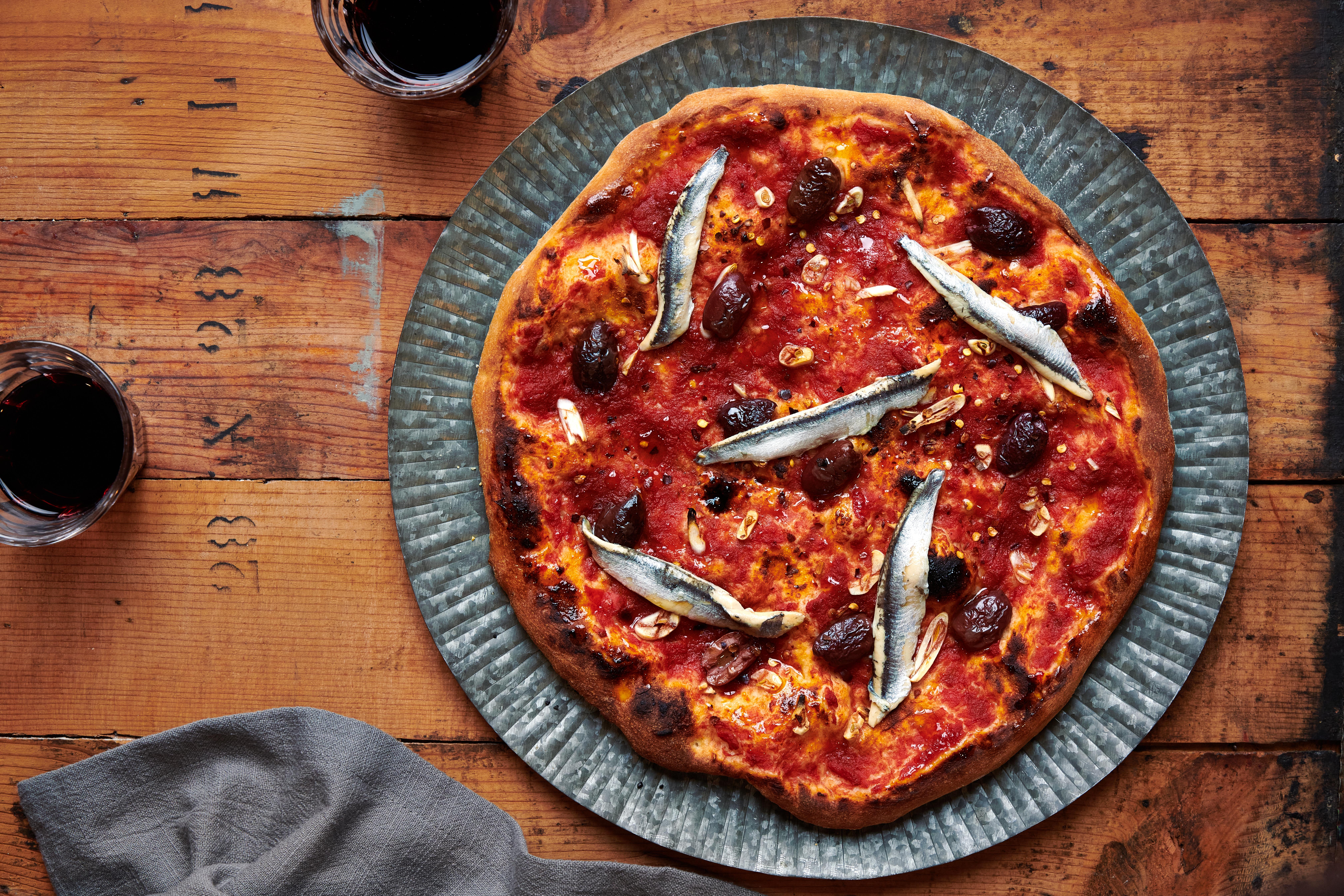 披萨配上西红柿酱,白色凤尾鱼和橄榄坐在一张木桌,与两杯红葡萄酒和灰色的餐巾。