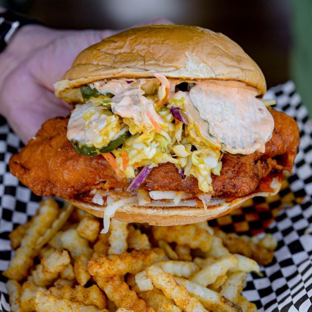 一只白手拿着溢出的鸡肉三明治溢出的泡菜和凉拌卷心菜在一个篮子上的奶油小圆面包与方格的纸和调味的皱纹剪切炸薯条上。