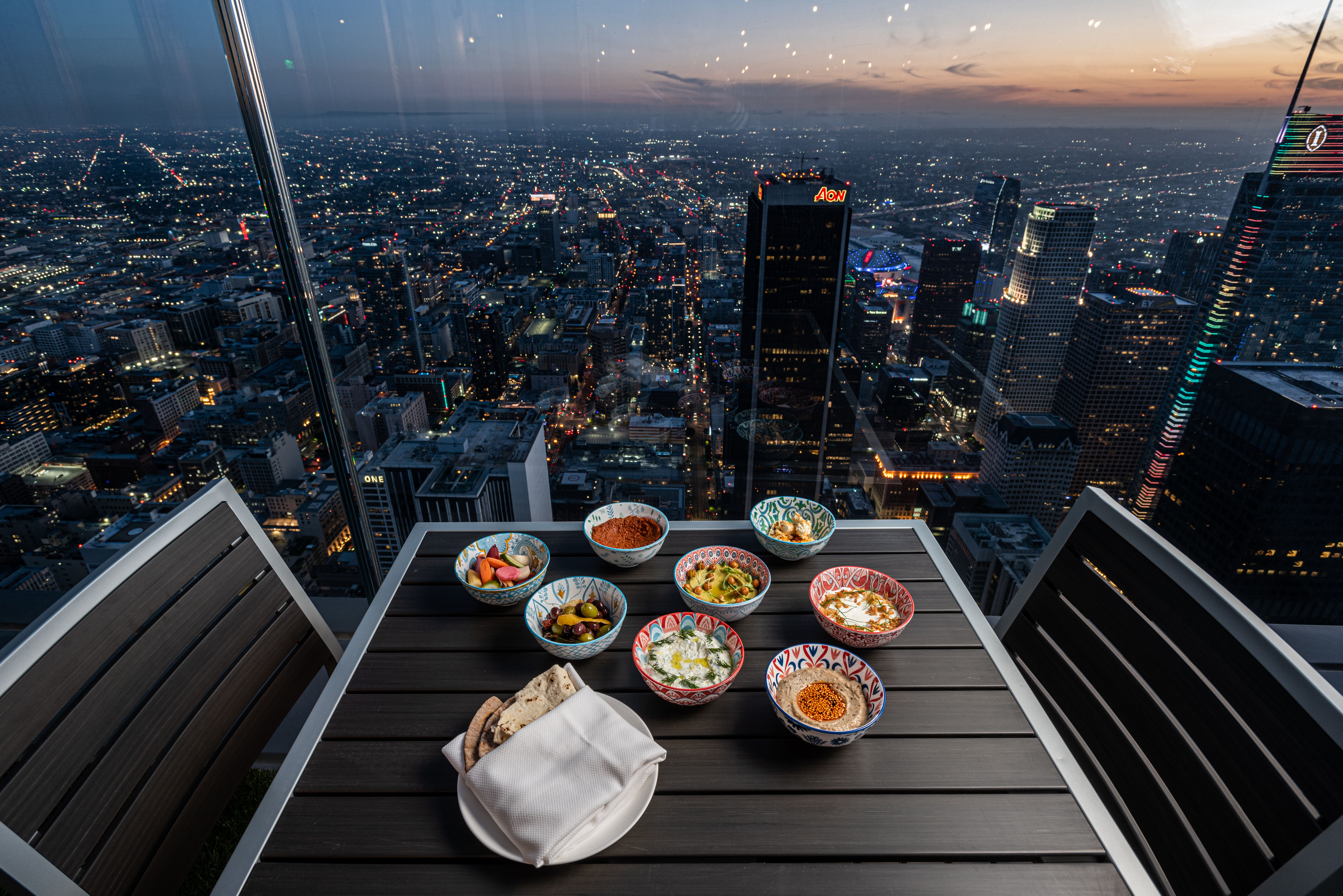A table set against a thick pane of glass above a twinkling city.