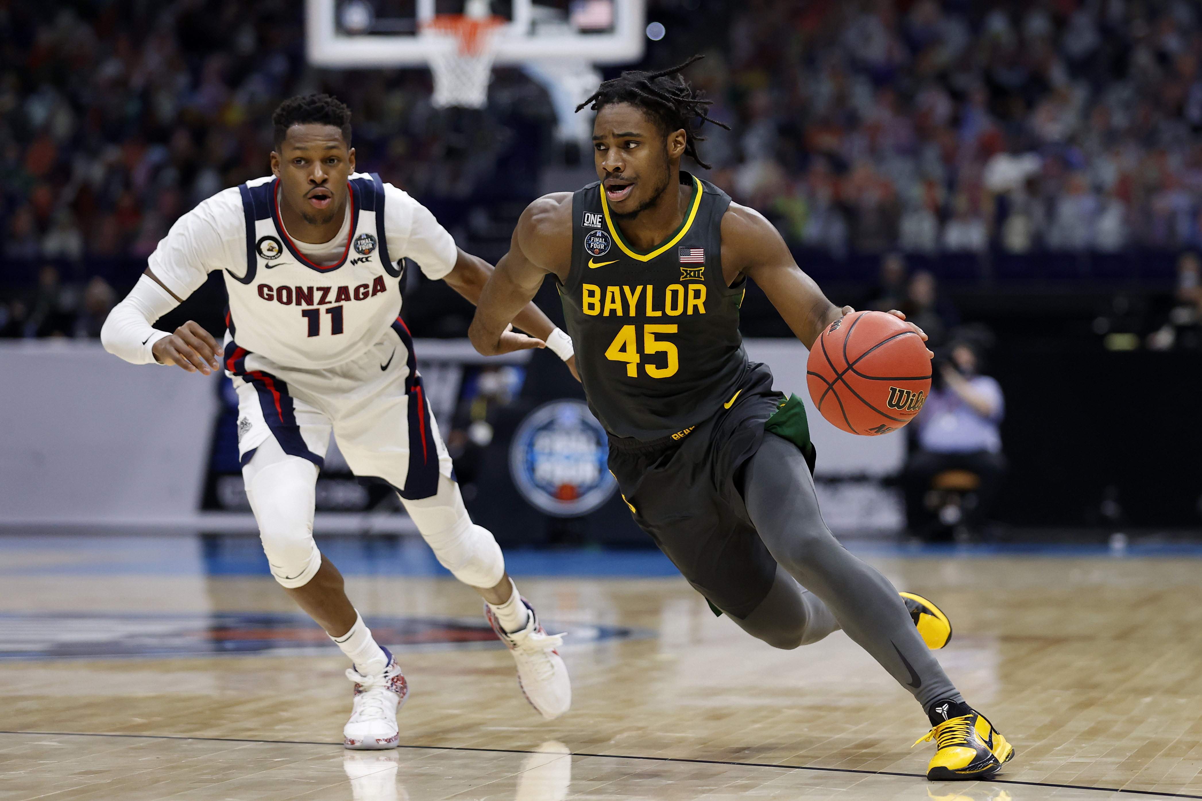 Davion Mitchell of the Baylor Bears drives to the basket as Joel Ayayi of the Gonzaga Bulldogs defends in the National Championship game of the 2021 NCAA Men's Basketball Tournament at Lucas Oil Stadium on April 05, 2021 in Indianapolis, Indiana.