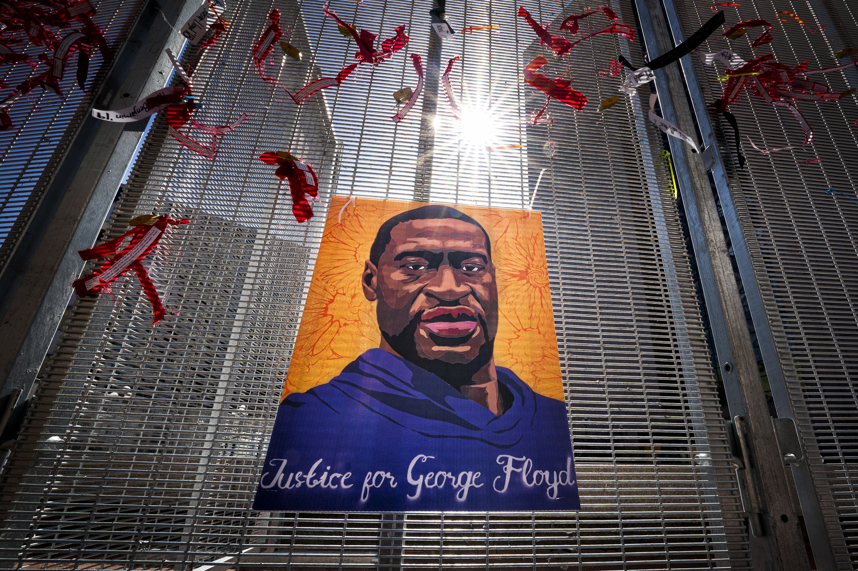 """A painting of George Floyd reading """"justice for George Floyd"""" hangs on a fence made of tight mesh. Red ribbons have been tied around the painting; these flap in the breeze, as the sun shines above the entire scene."""