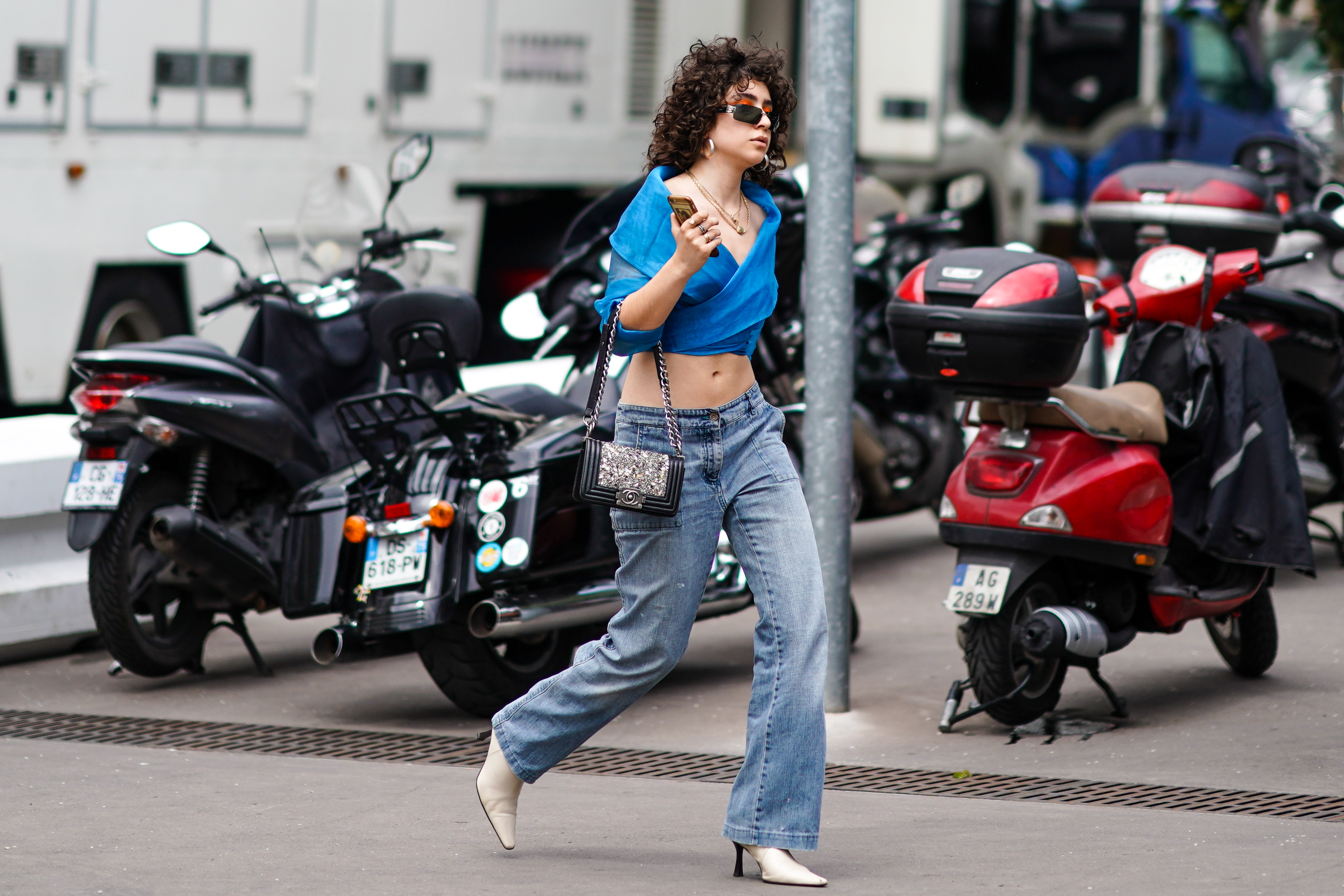 A woman wearing low-rise jeans and a crop top while walking down the street.