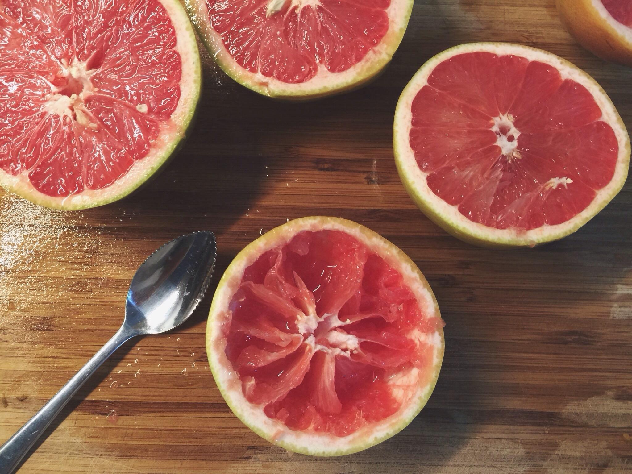 一把葡萄柚勺子坐在木质表面上包围着减半的葡萄柚。