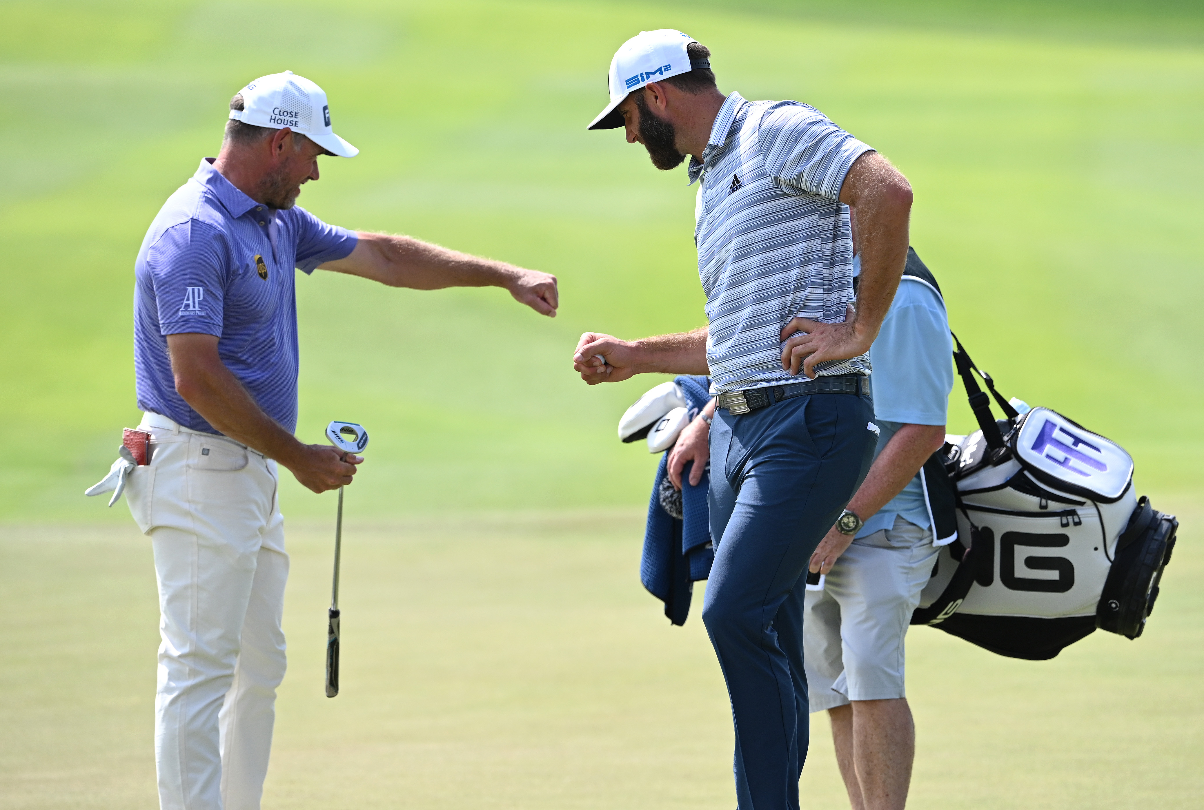 Lee Westwood of England (L) and Dustin Johnson of the USA (R) fist pump on the 9th green during Day One of the Saudi International powered by SoftBank Investment Advisers at Royal Greens Golf and Country Club on February 04, 2021 in King Abdullah Economic City, Saudi Arabia.