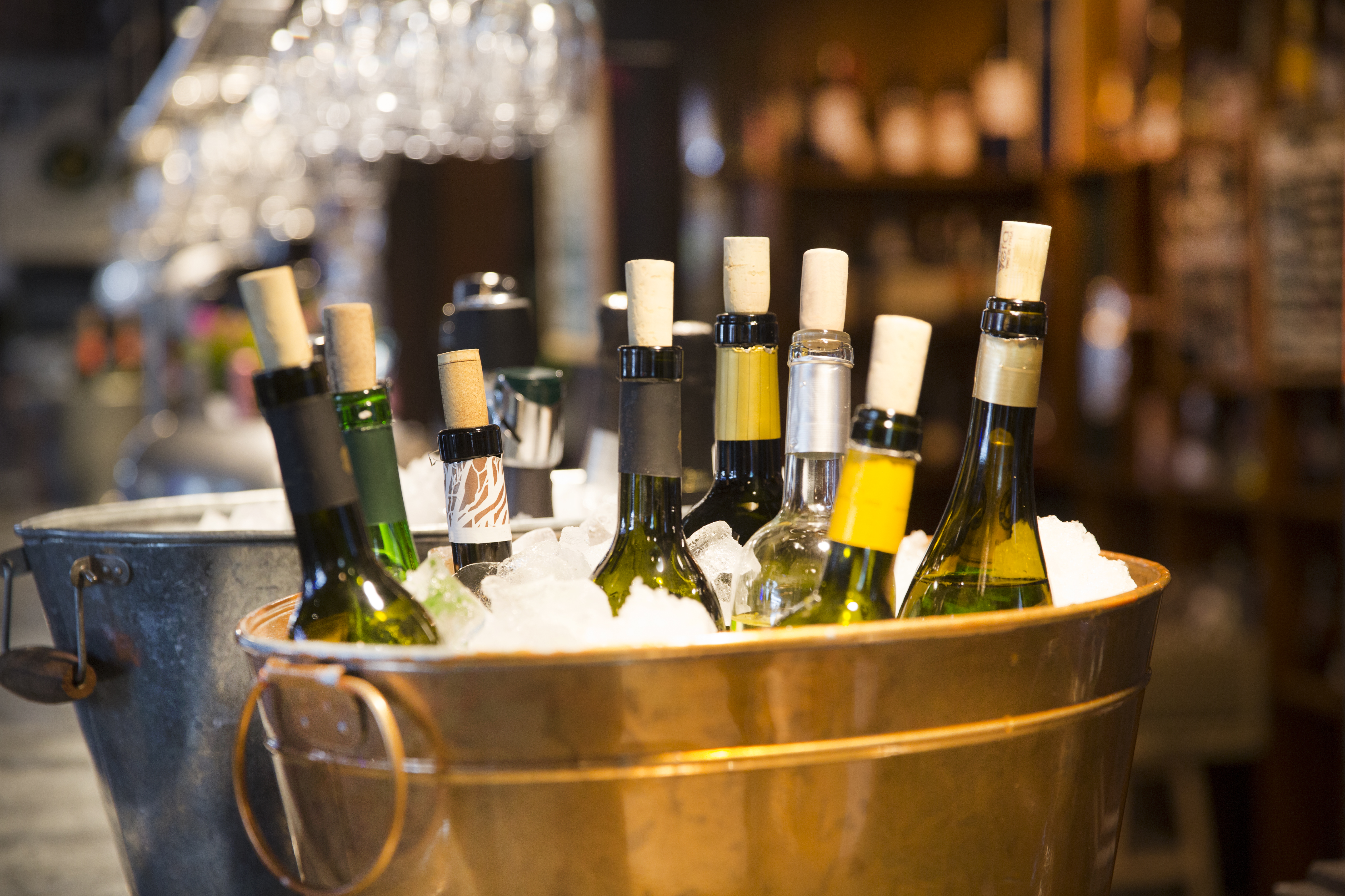Bottles of wine chilling in a big brass ice bucket, on a countertop