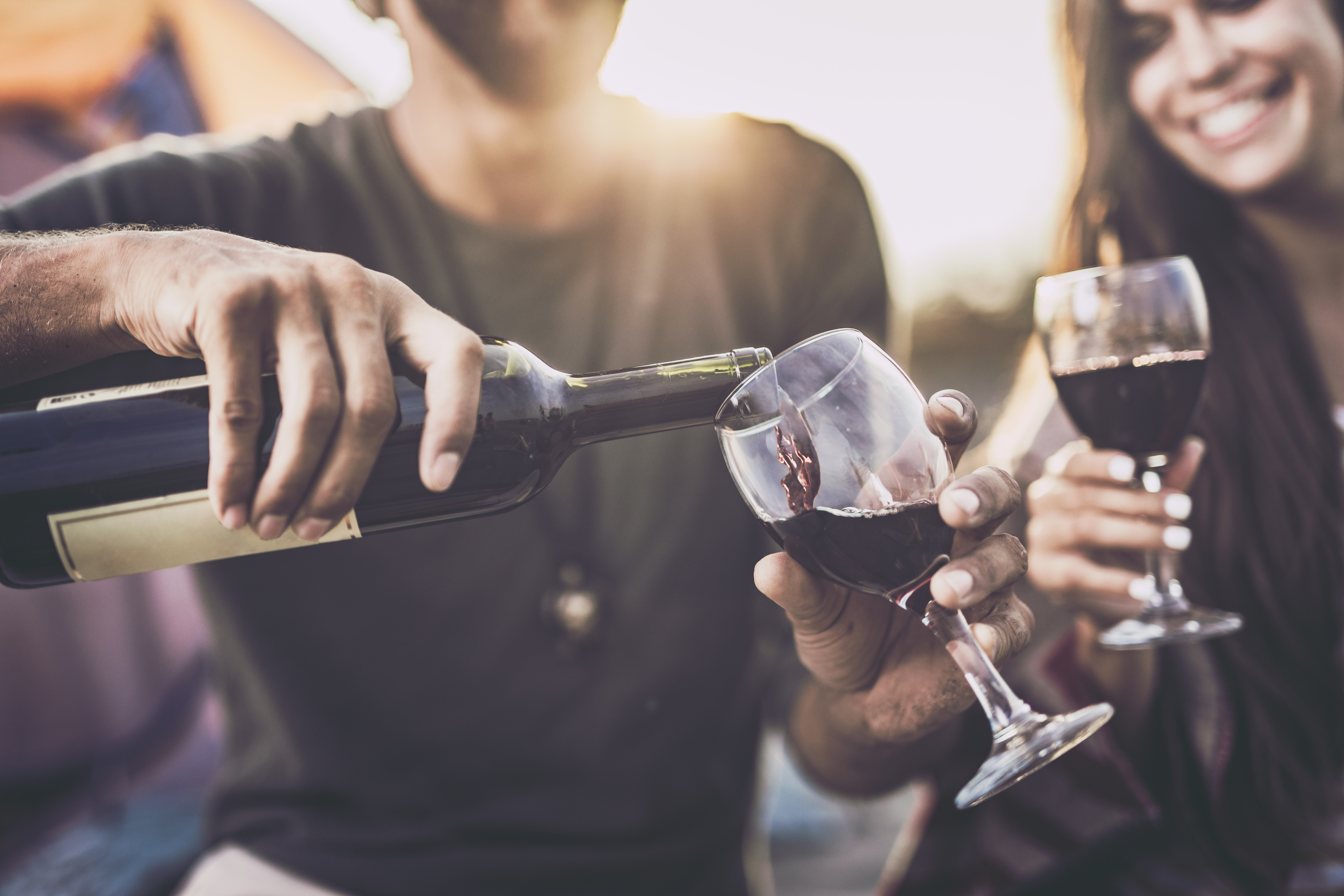 Closeup of a white smiling couple drinking red wine outdoors with sun in background while man is pouring it into a glass.